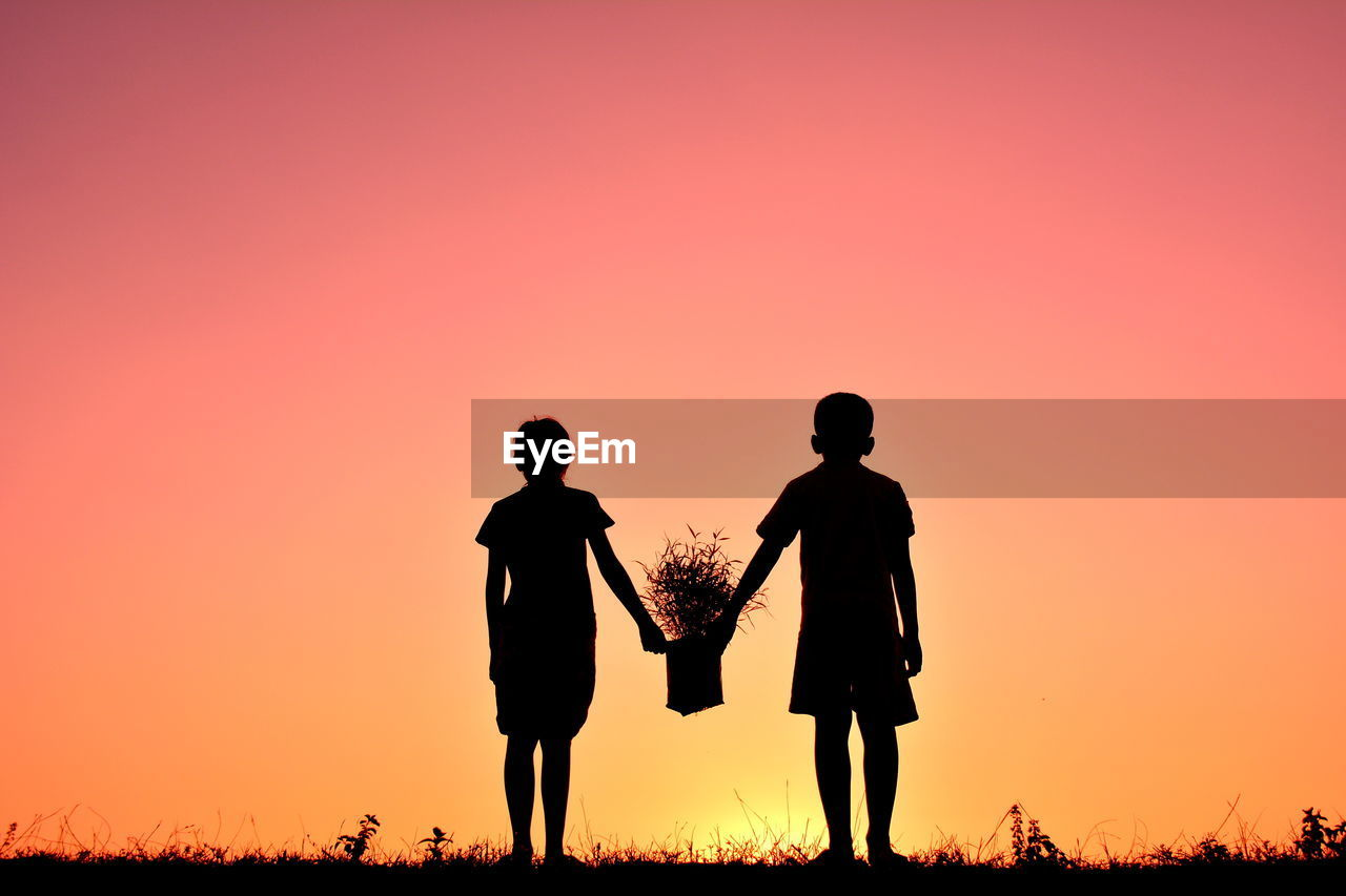 sunset, sky, orange color, real people, togetherness, lifestyles, two people, standing, men, beauty in nature, leisure activity, silhouette, people, field, copy space, land, nature, rear view, full length, clear sky, outdoors, couple - relationship