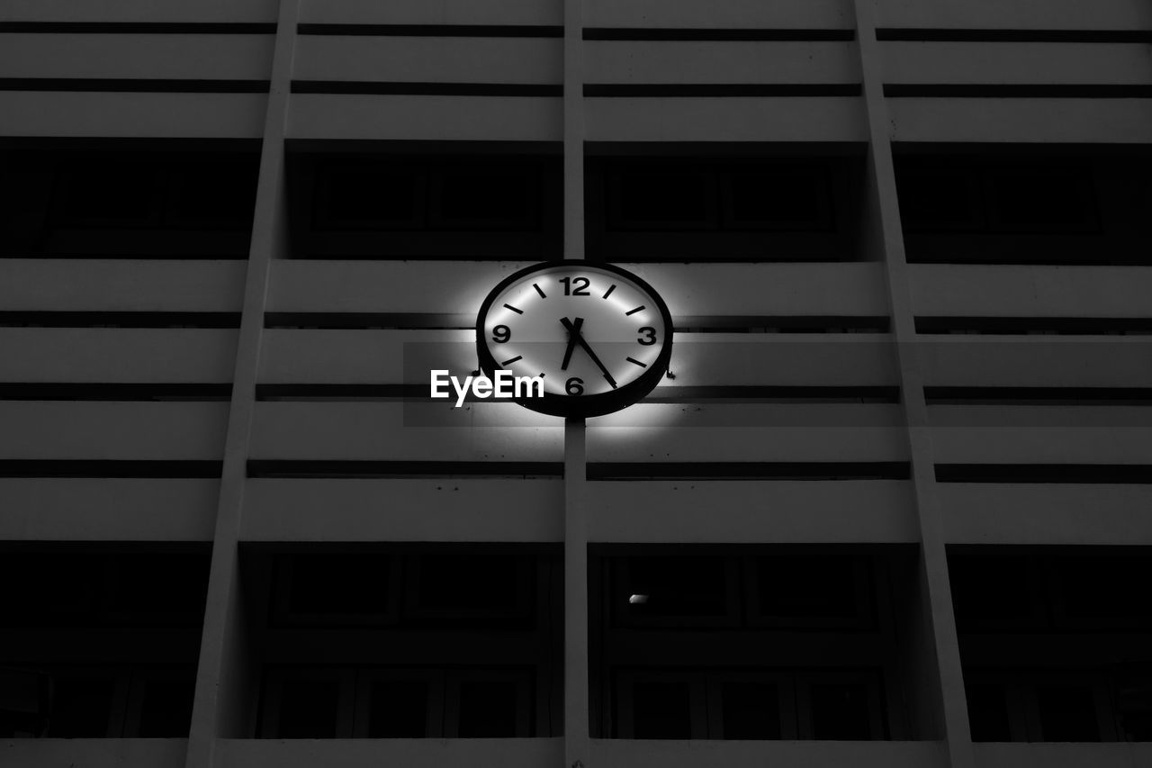 clock, built structure, time, architecture, low angle view, building, building exterior, no people, geometric shape, night, shape, window, outdoors, instrument of time, clock face, circle, wall - building feature, illuminated, number, minute hand, wall clock