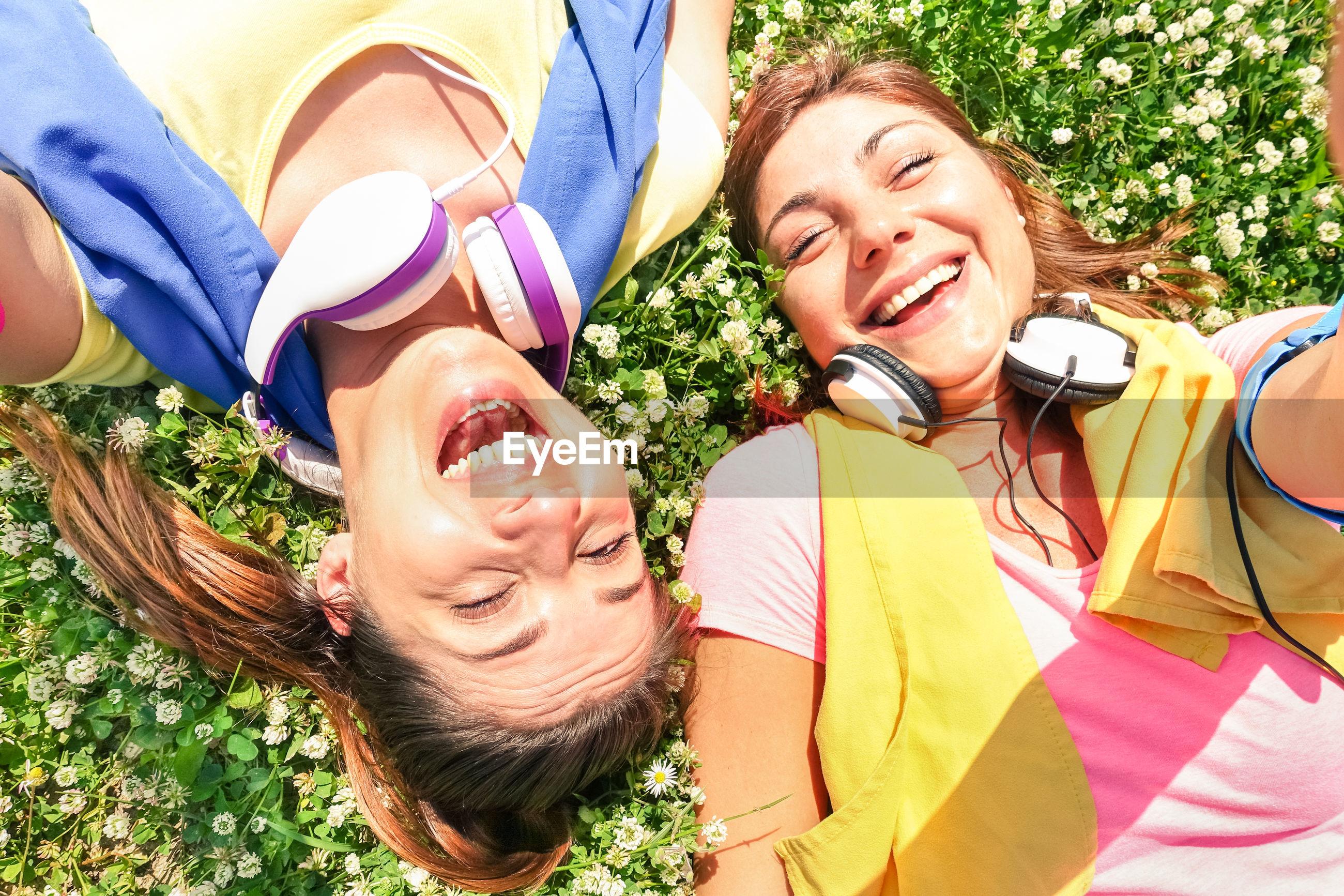Portrait of smiling women lying on field