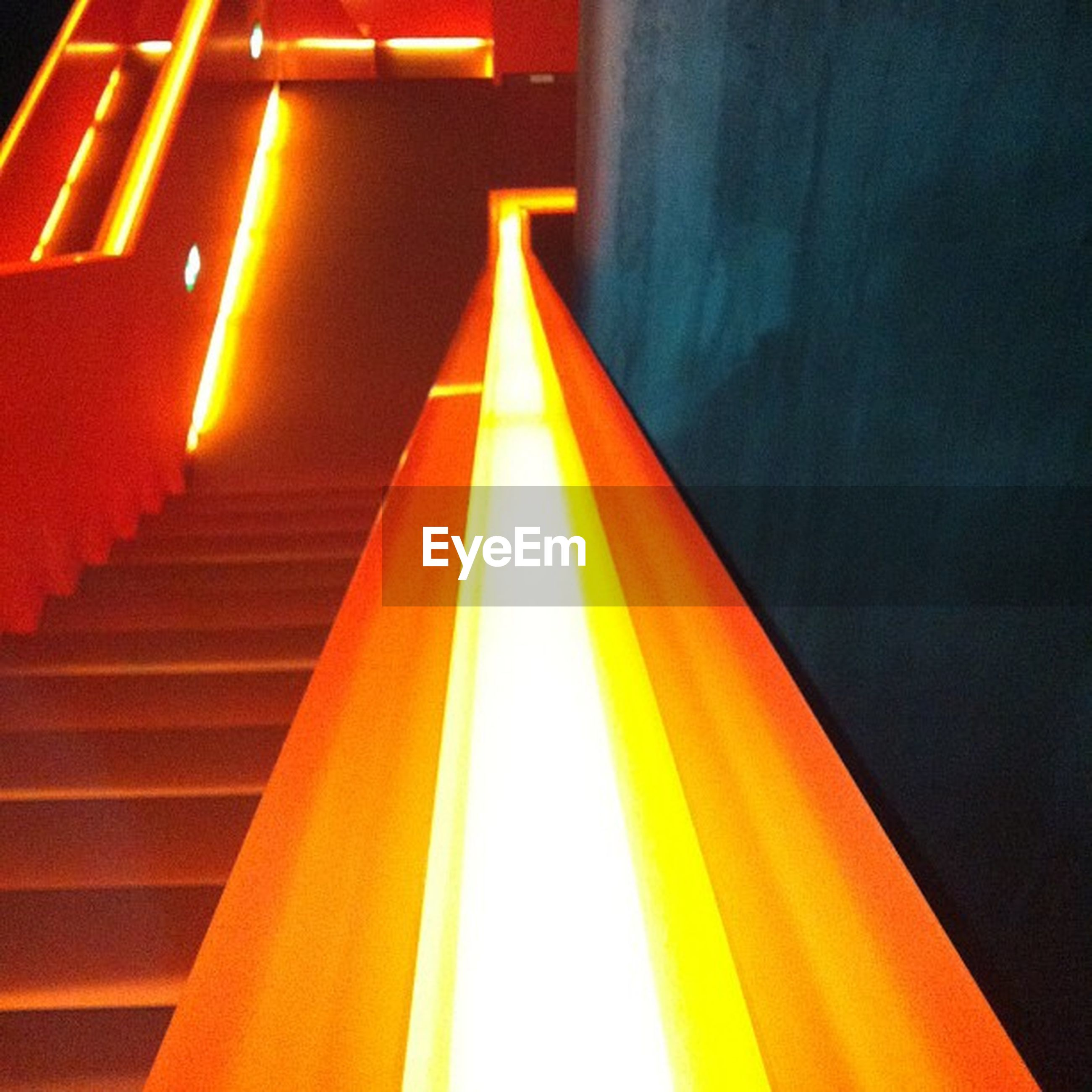illuminated, indoors, built structure, architecture, steps, steps and staircases, staircase, lighting equipment, low angle view, the way forward, night, wall - building feature, railing, light - natural phenomenon, diminishing perspective, pattern, no people, building, ceiling, glowing