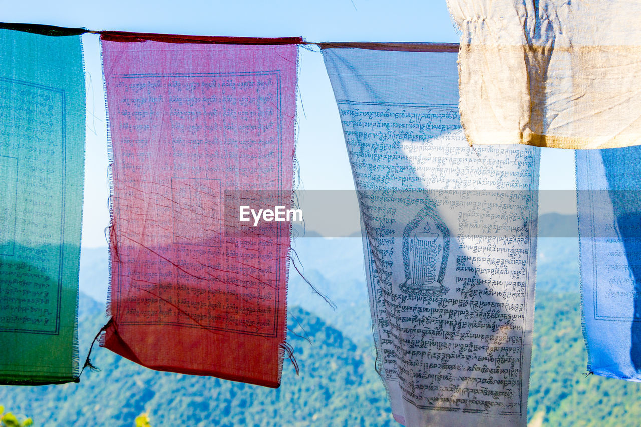 hanging, textile, day, no people, multi colored, nature, flag, communication, sunlight, focus on foreground, blue, close-up, clothing, outdoors, text, clothesline, curtain, transparent, material, drying