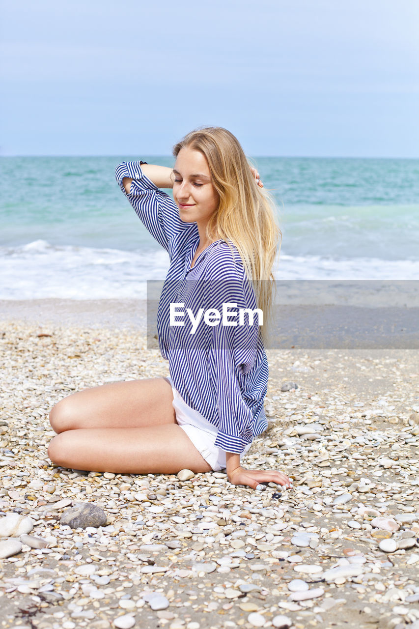 beach, sea, land, water, one person, leisure activity, lifestyles, young women, young adult, real people, horizon, hair, beauty in nature, horizon over water, sky, long hair, blond hair, hairstyle, beautiful woman, outdoors