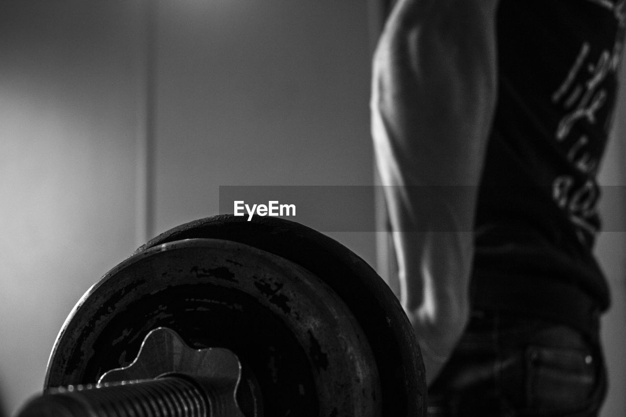 Midsection Of Man Lifting Weights In Gym