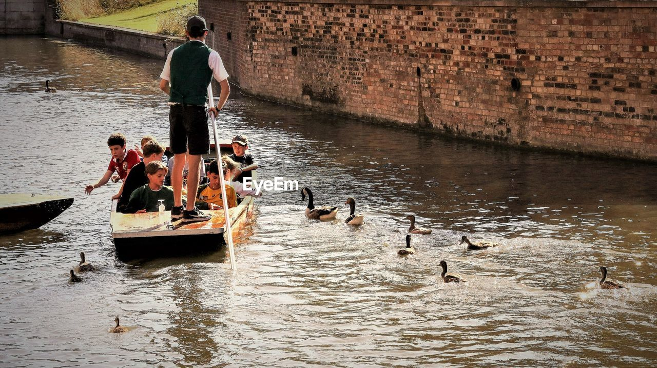 water, river, large group of animals, waterfront, day, men, real people, nautical vessel, animal wildlife, large group of people, animals in the wild, outdoors, nature, bird, architecture, adult, people, adults only