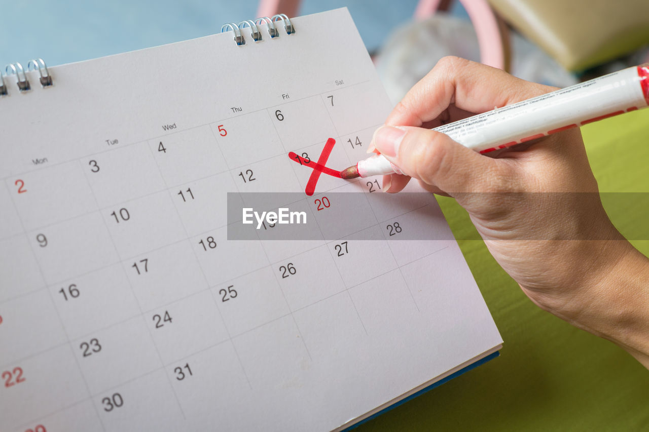 Cropped hand crossing date on calendar