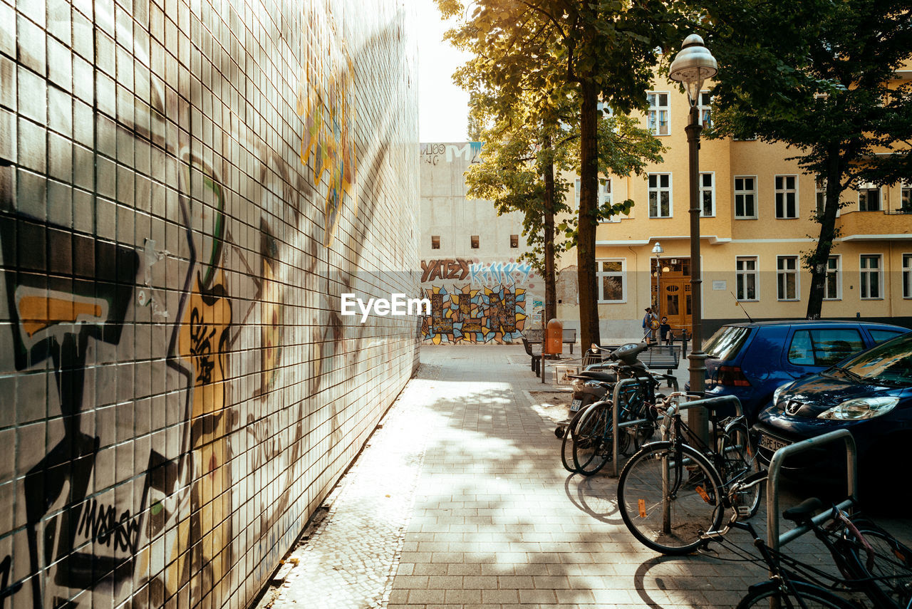 architecture, built structure, building exterior, transportation, building, bicycle, mode of transportation, tree, city, land vehicle, plant, no people, nature, day, street, residential district, stationary, sunlight, outdoors, direction, alley
