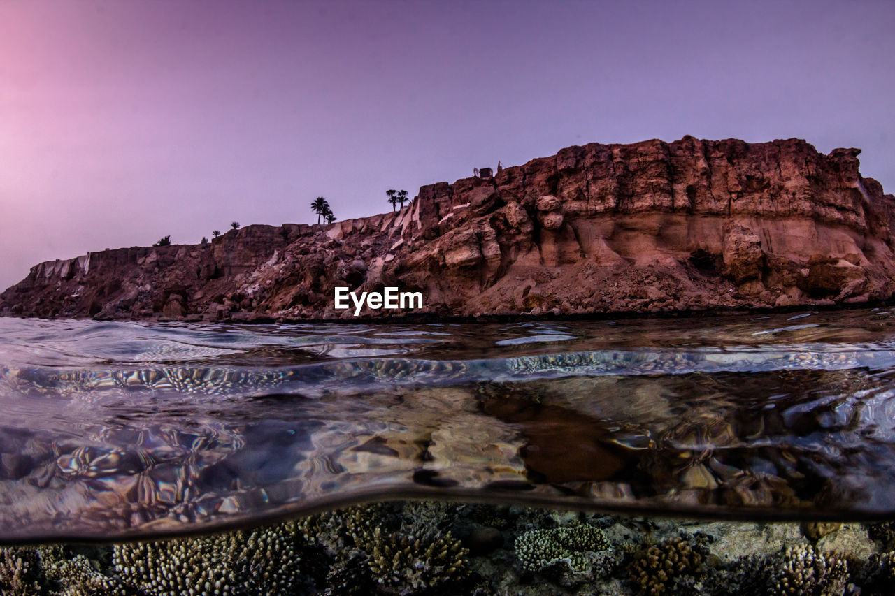 Scenic View Of Sea And Rock Formation Against Clear Sky During Sunset