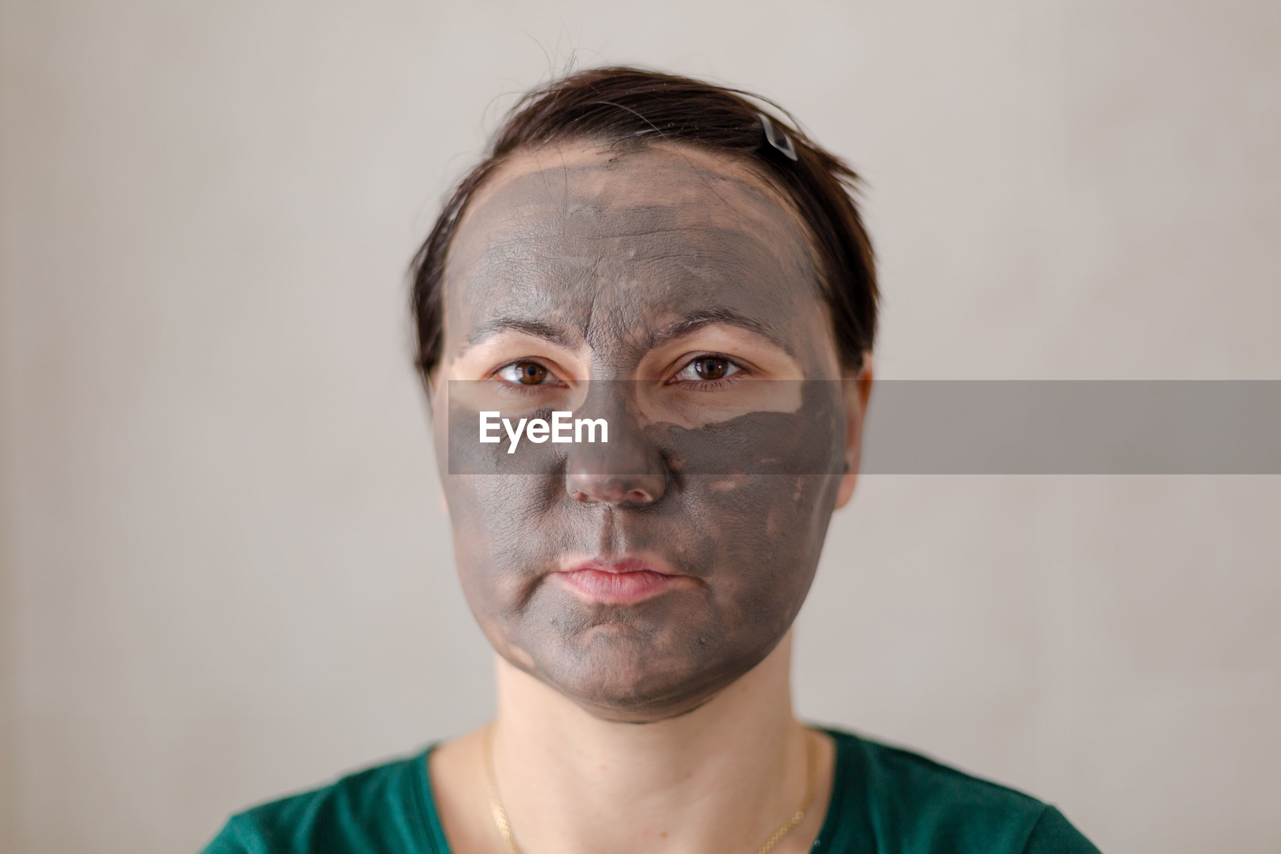 Portrait of mid adult woman with facial mask standing against wall