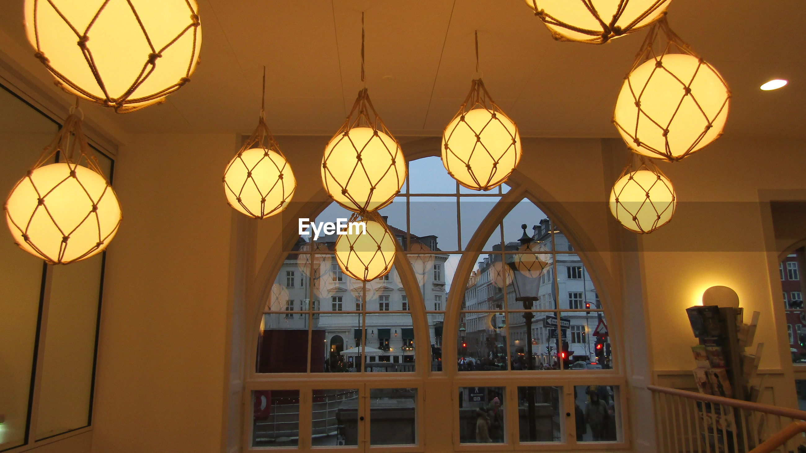 LOW ANGLE VIEW OF ILLUMINATED PENDANT LIGHTS HANGING ON CEILING OF BUILDING