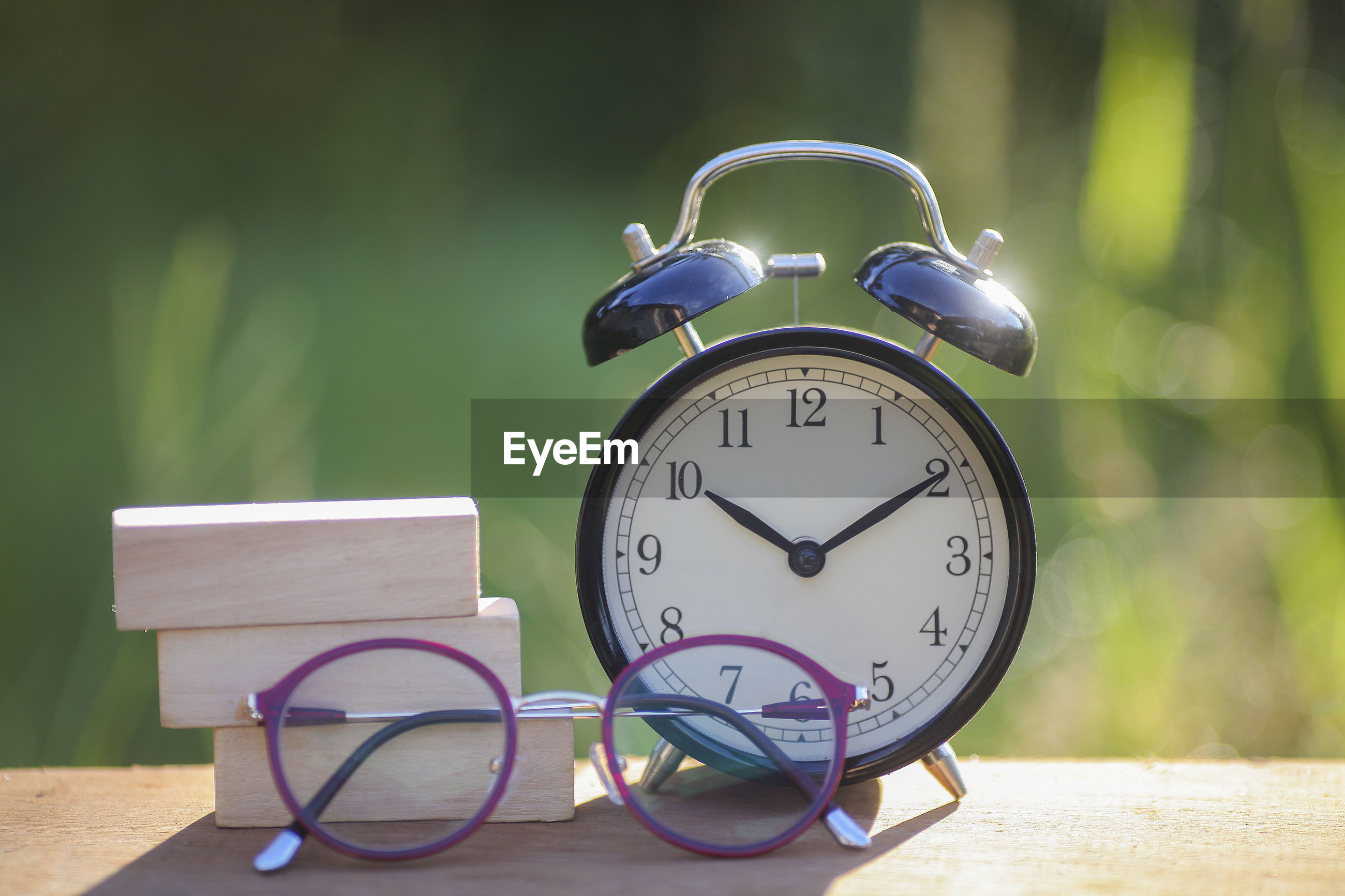Close-up of eyeglasses by book and alarm clock on table