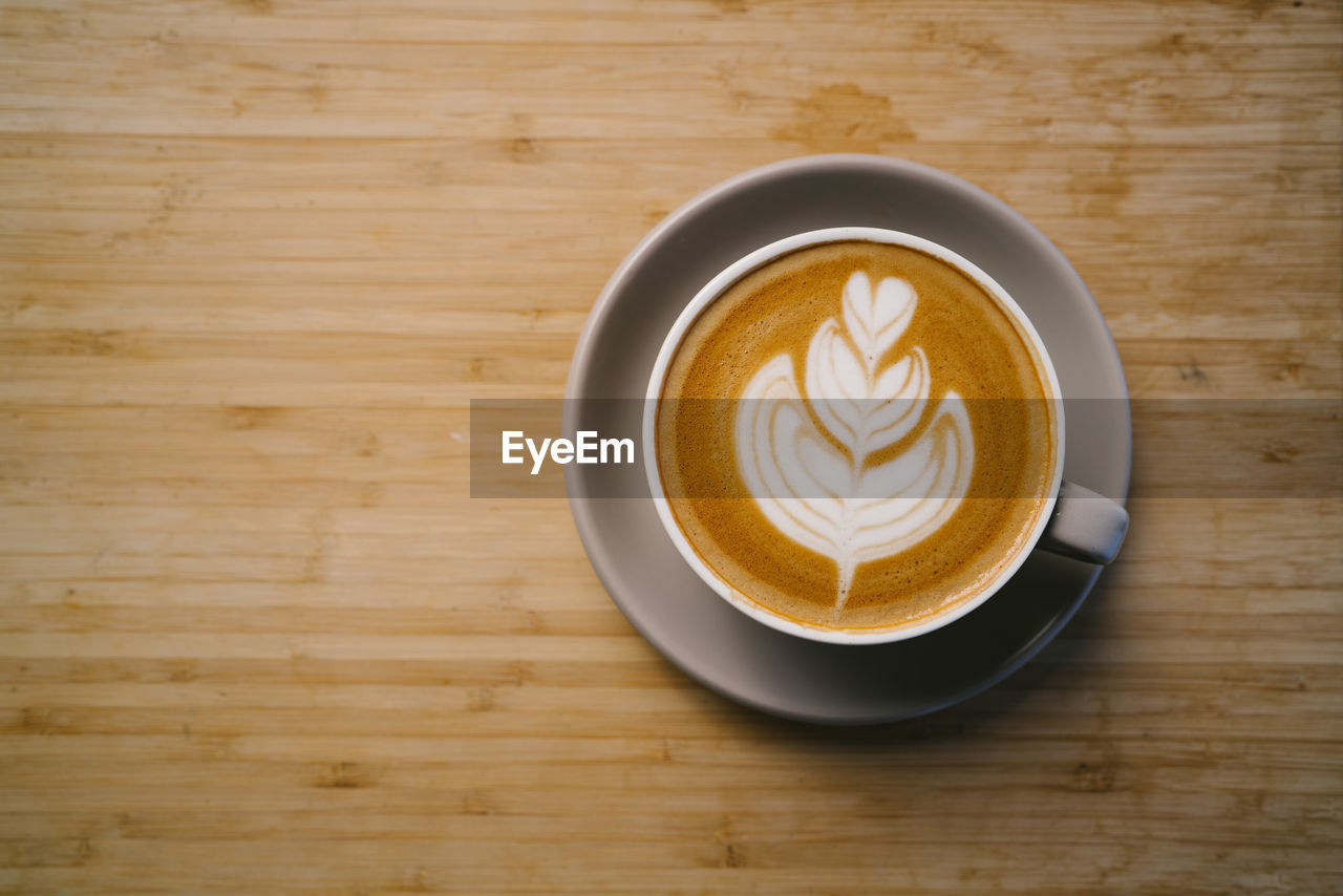 refreshment, food and drink, coffee - drink, drink, coffee, cup, mug, coffee cup, still life, frothy drink, table, hot drink, freshness, indoors, saucer, froth art, crockery, wood - material, cappuccino, directly above, latte, no people, non-alcoholic beverage, wood grain