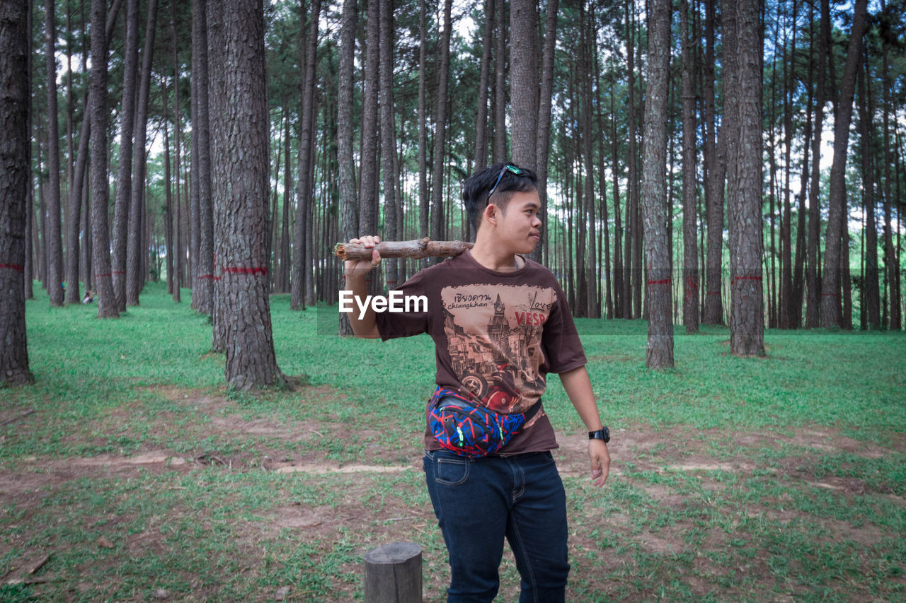 tree, plant, one person, land, forest, standing, three quarter length, holding, young adult, front view, nature, woodland, casual clothing, day, grass, tree trunk, trunk, adult, real people, outdoors