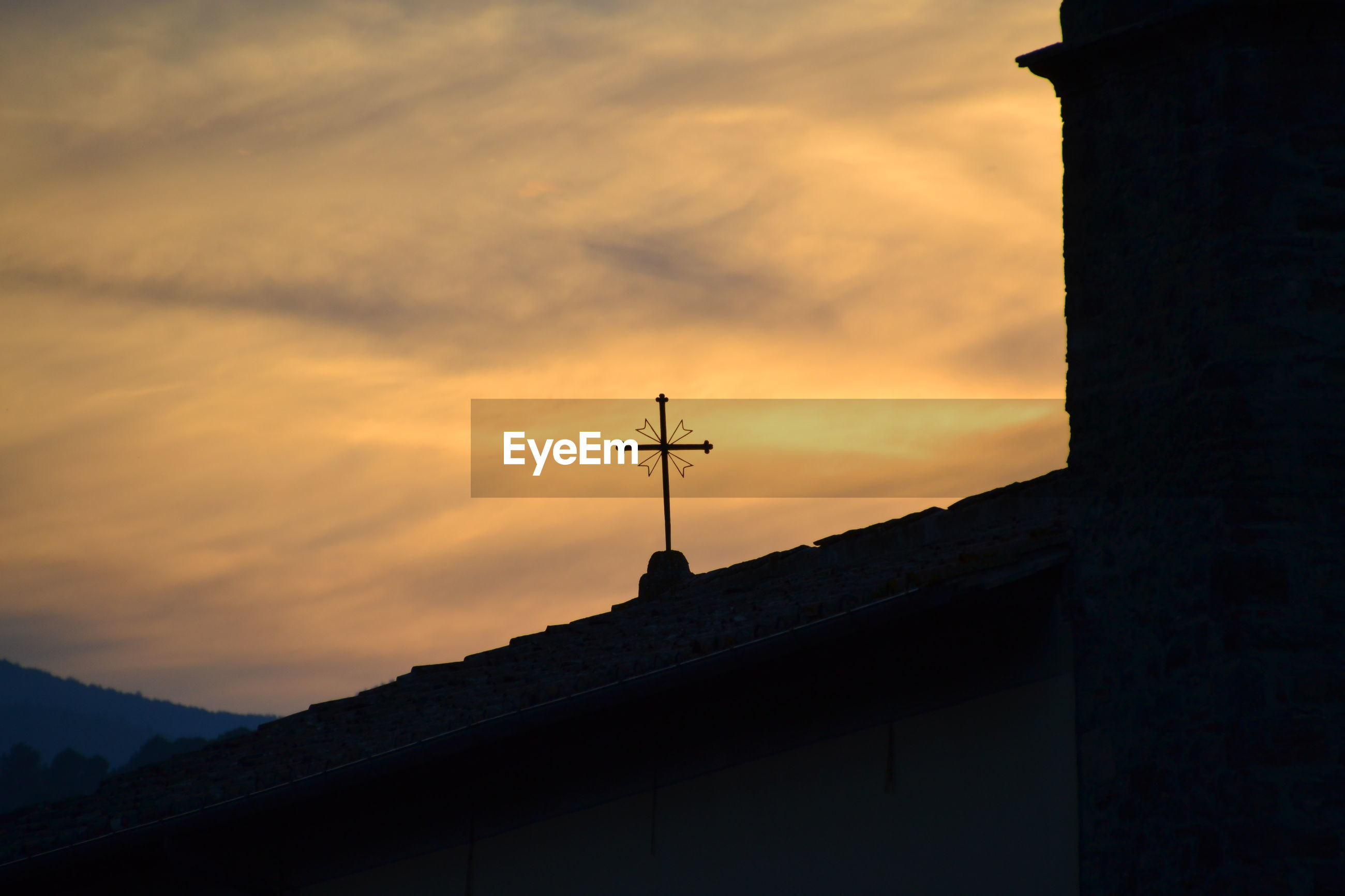 Low angle view of weather vane and cross against sky at sunset