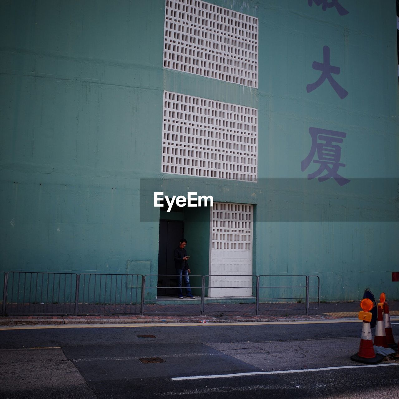 Man reading message on phone at entrance of building