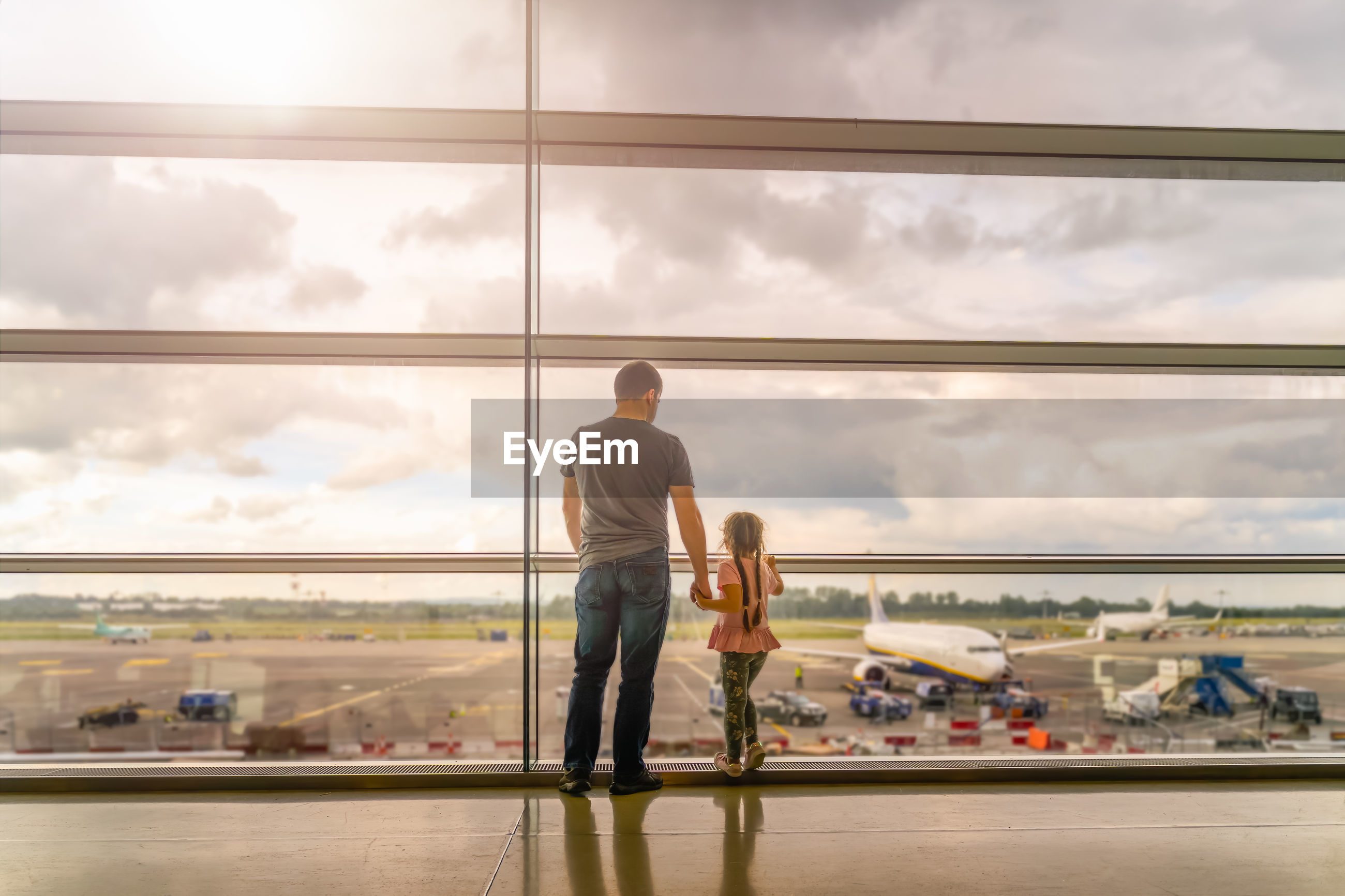 REAR VIEW OF MEN SITTING ON AIRPORT WINDOW