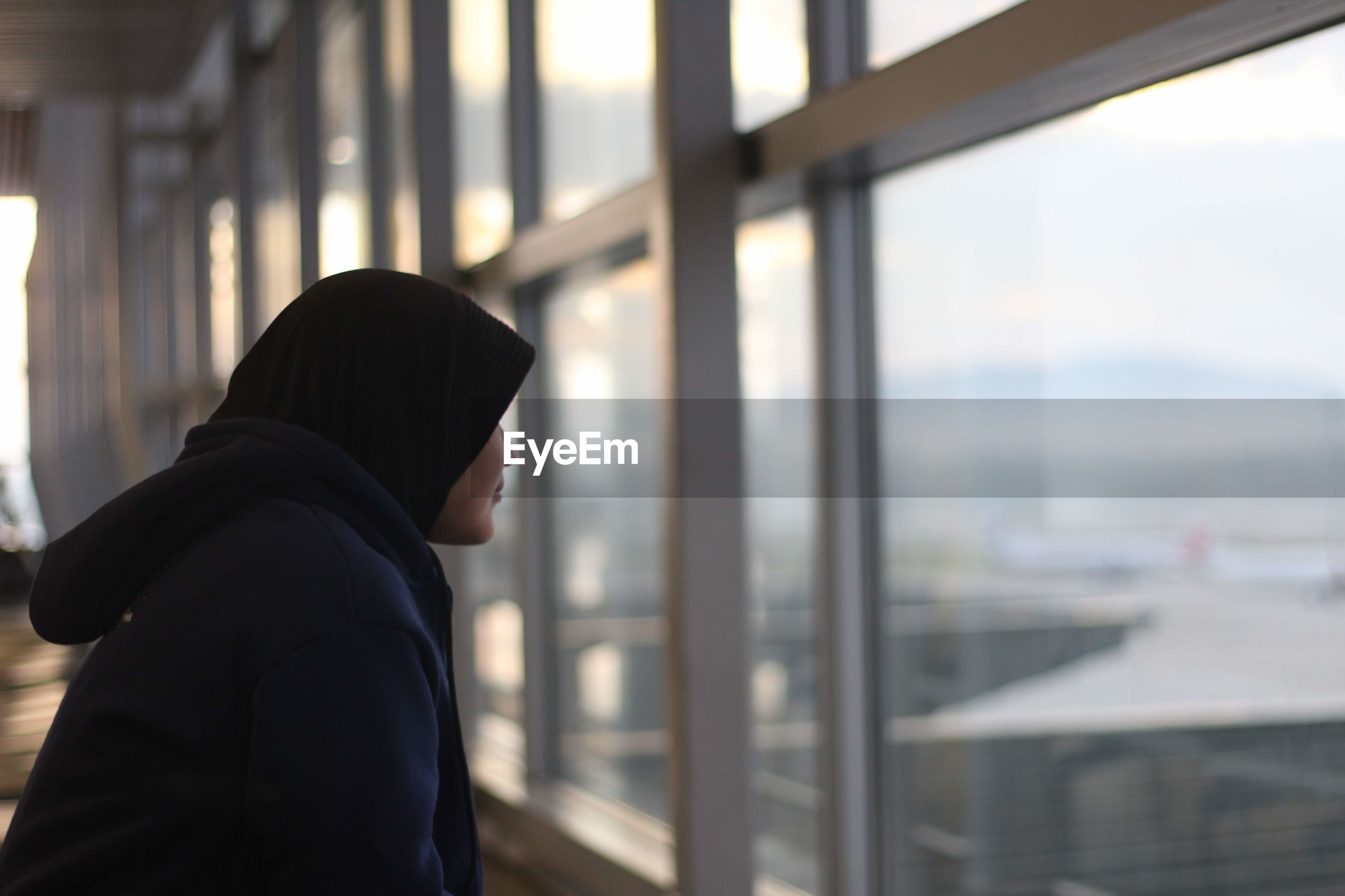 Woman wearing hijab while looking through window at airport