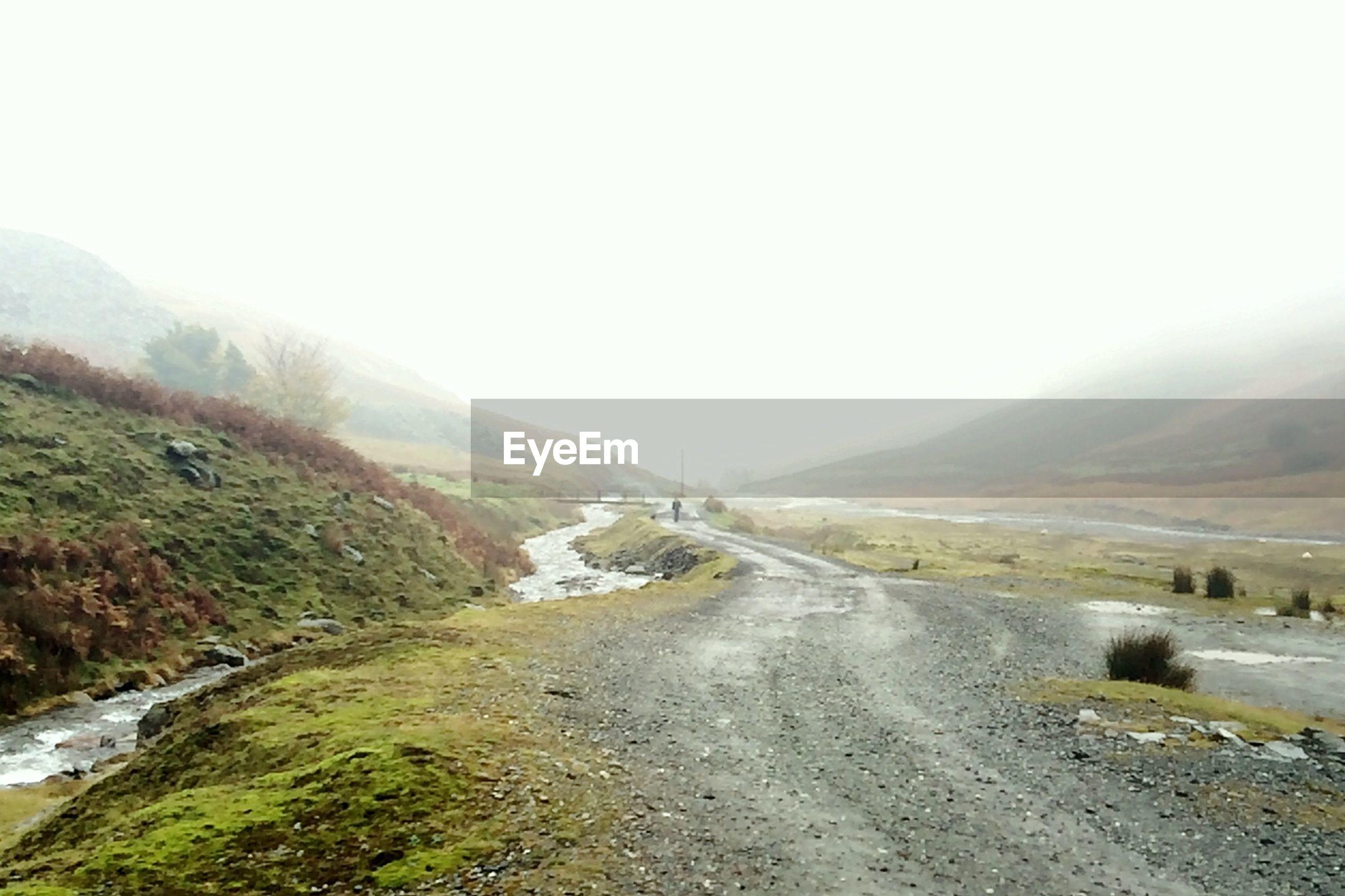 Road leading towards foggy mountains