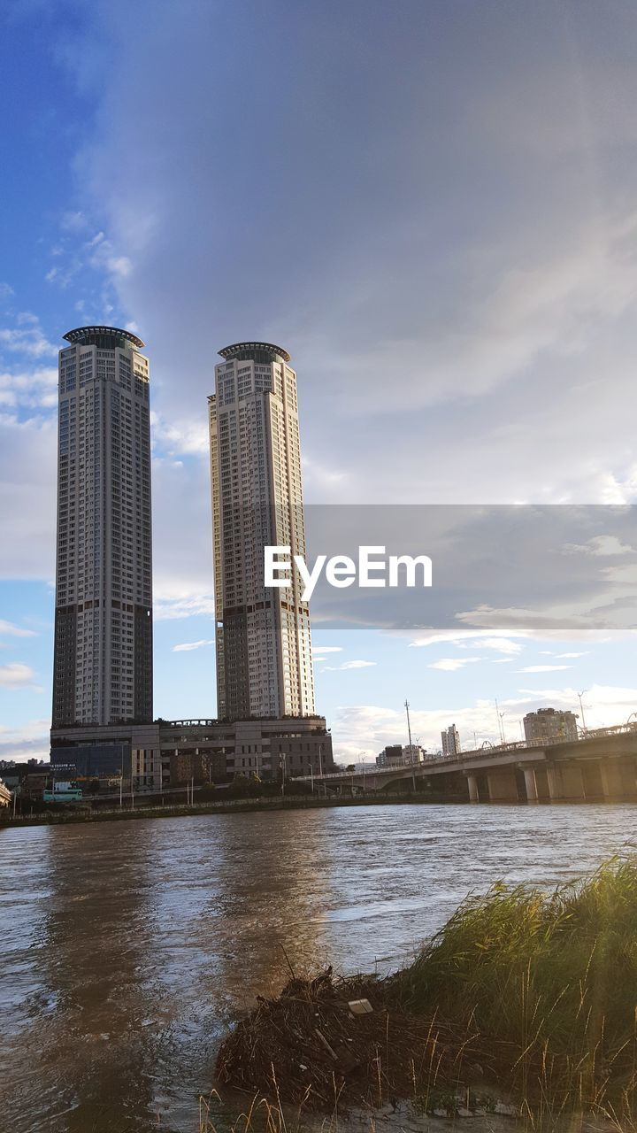 sky, built structure, architecture, cloud - sky, water, building exterior, nature, river, no people, day, waterfront, industry, outdoors, tall - high, tower, factory, sunlight, city, building, skyscraper