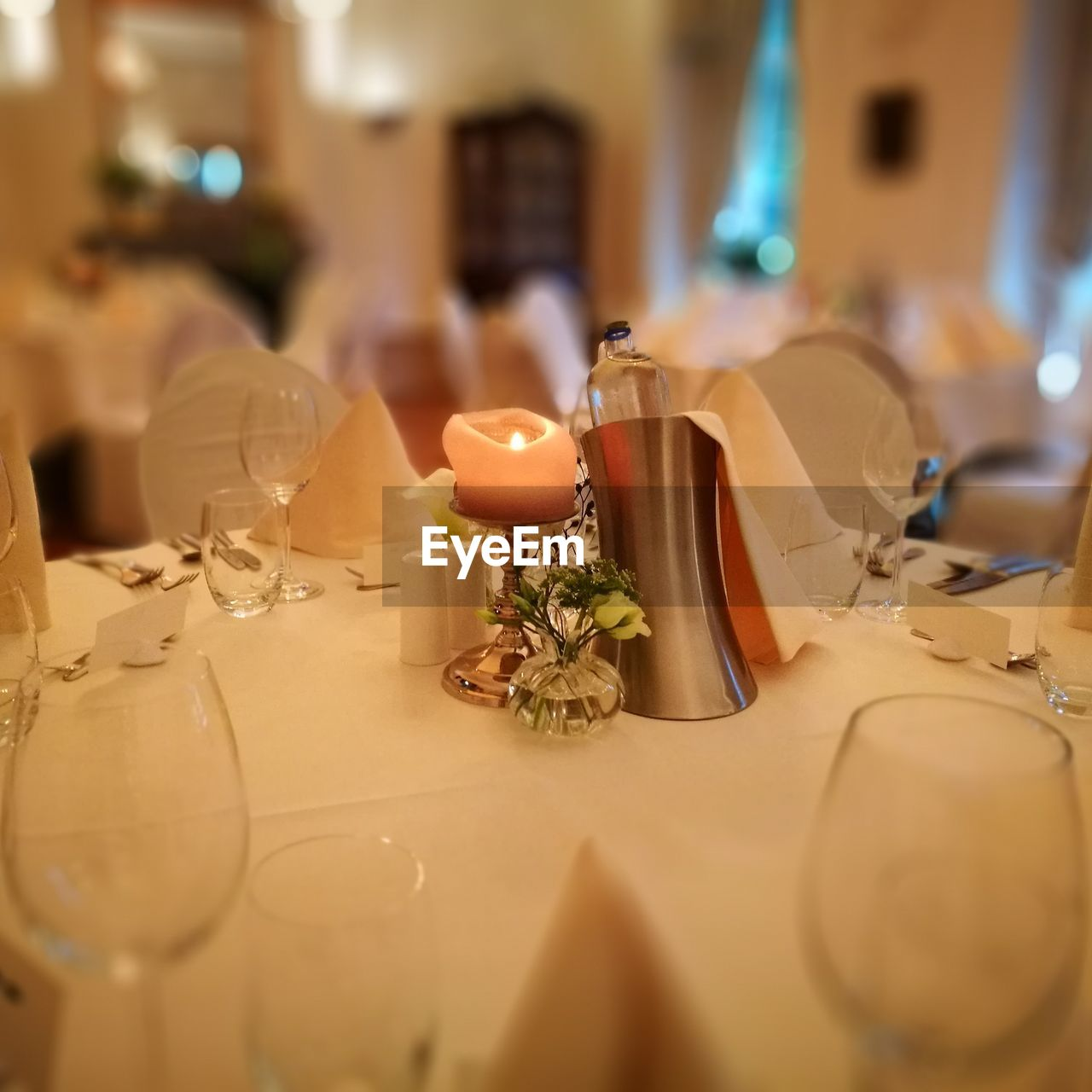 table, place setting, candle, plate, indoors, dining table, fork, restaurant, table knife, wineglass, wedding, celebration, napkin, food and drink, tea light, no people, drinking glass, centerpiece, close-up, tablecloth, food, illuminated, night, flower