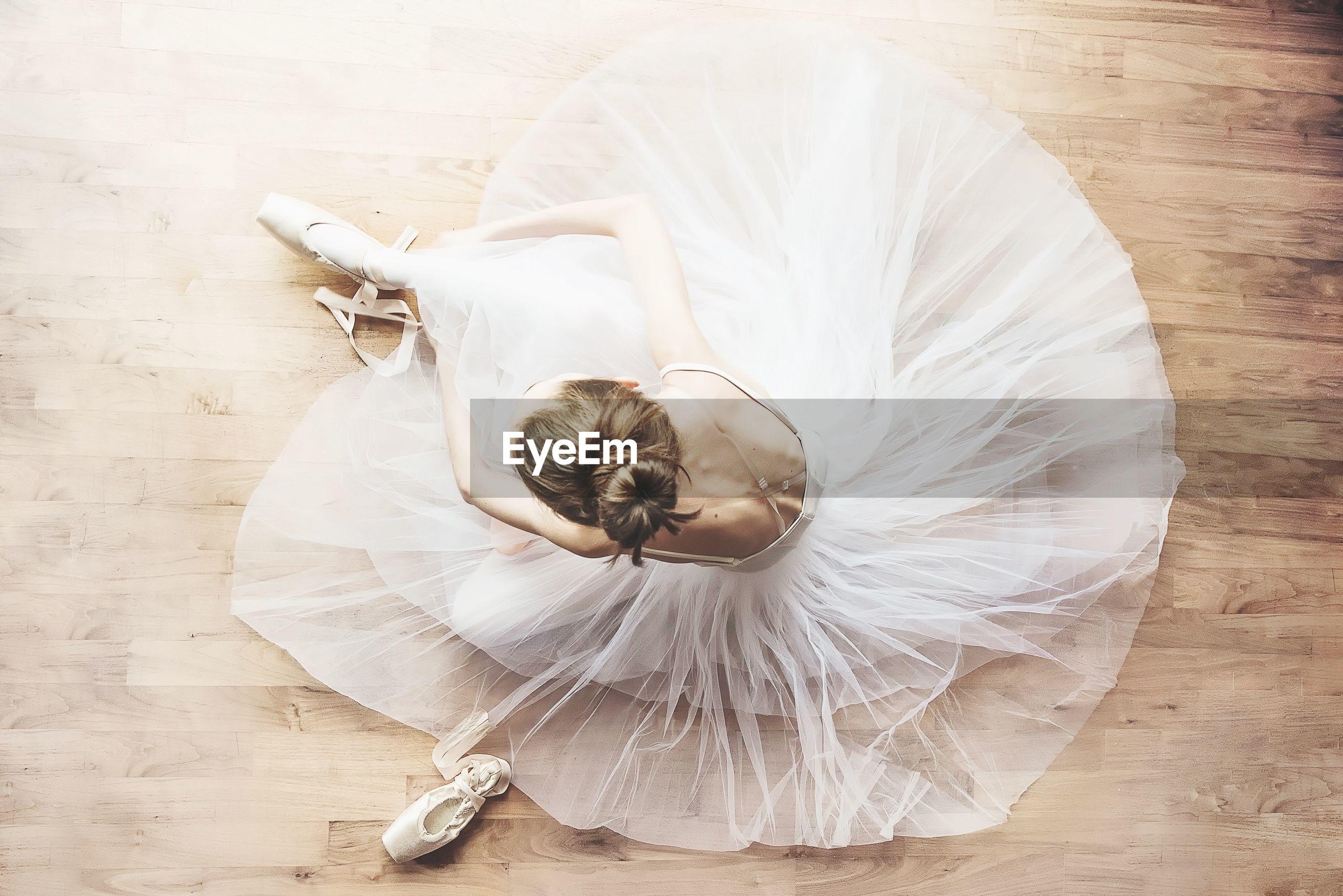 High angle view of ballerina sitting on hardwood floor