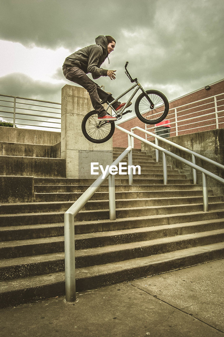 stunt, bicycle, jumping, bmx cycling, leisure activity, risk, full length, mid-air, staircase, skill, extreme sports, recreational pursuit, lifestyles, one person, railing, men, riding, real people, sky, cloud - sky, sports ramp, outdoors, steps, skateboard park, day, built structure, fun, low angle view, adventure, exercising, young adult, stunt person, people, adult