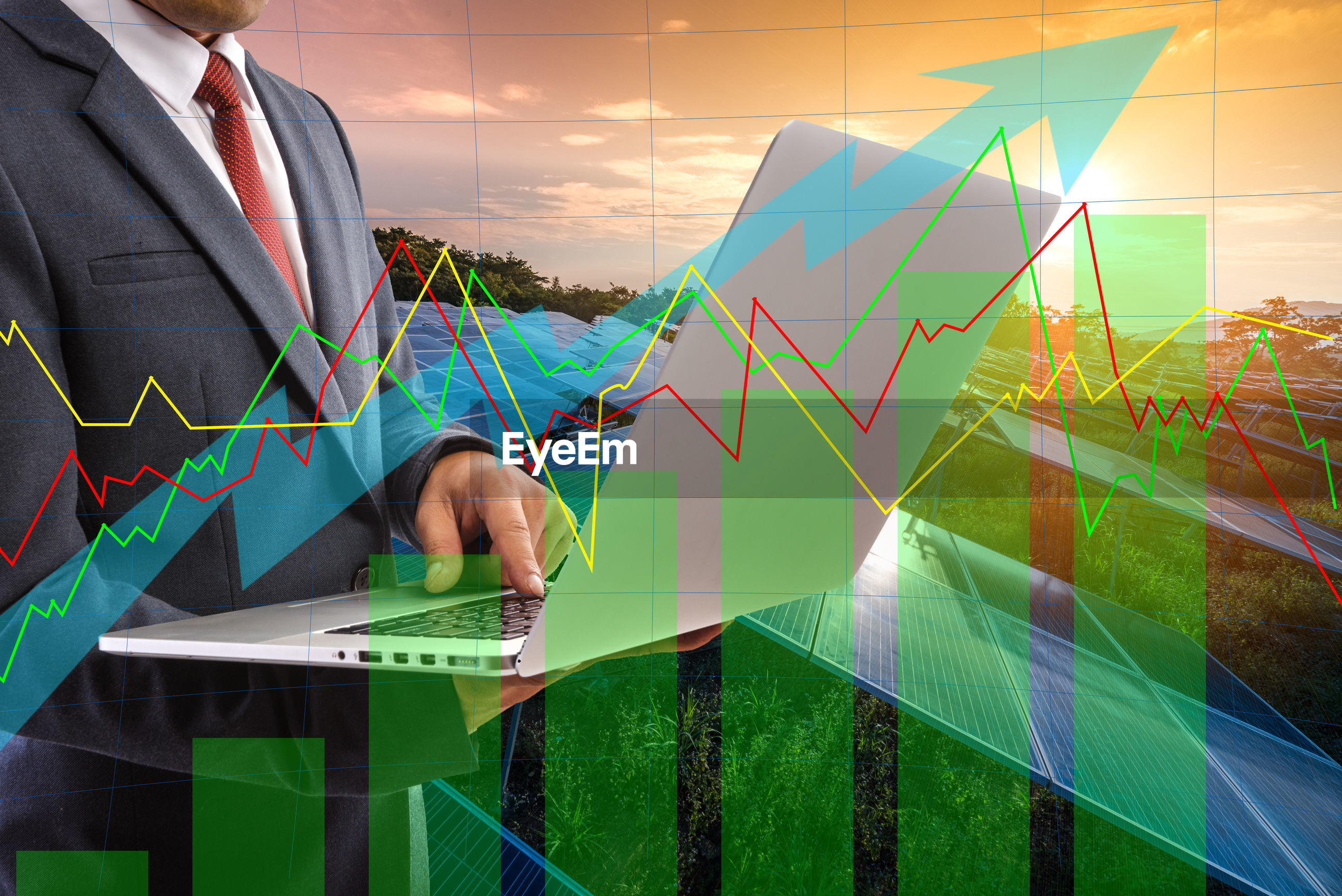 Digital composite image of businessman using laptop by solar panels