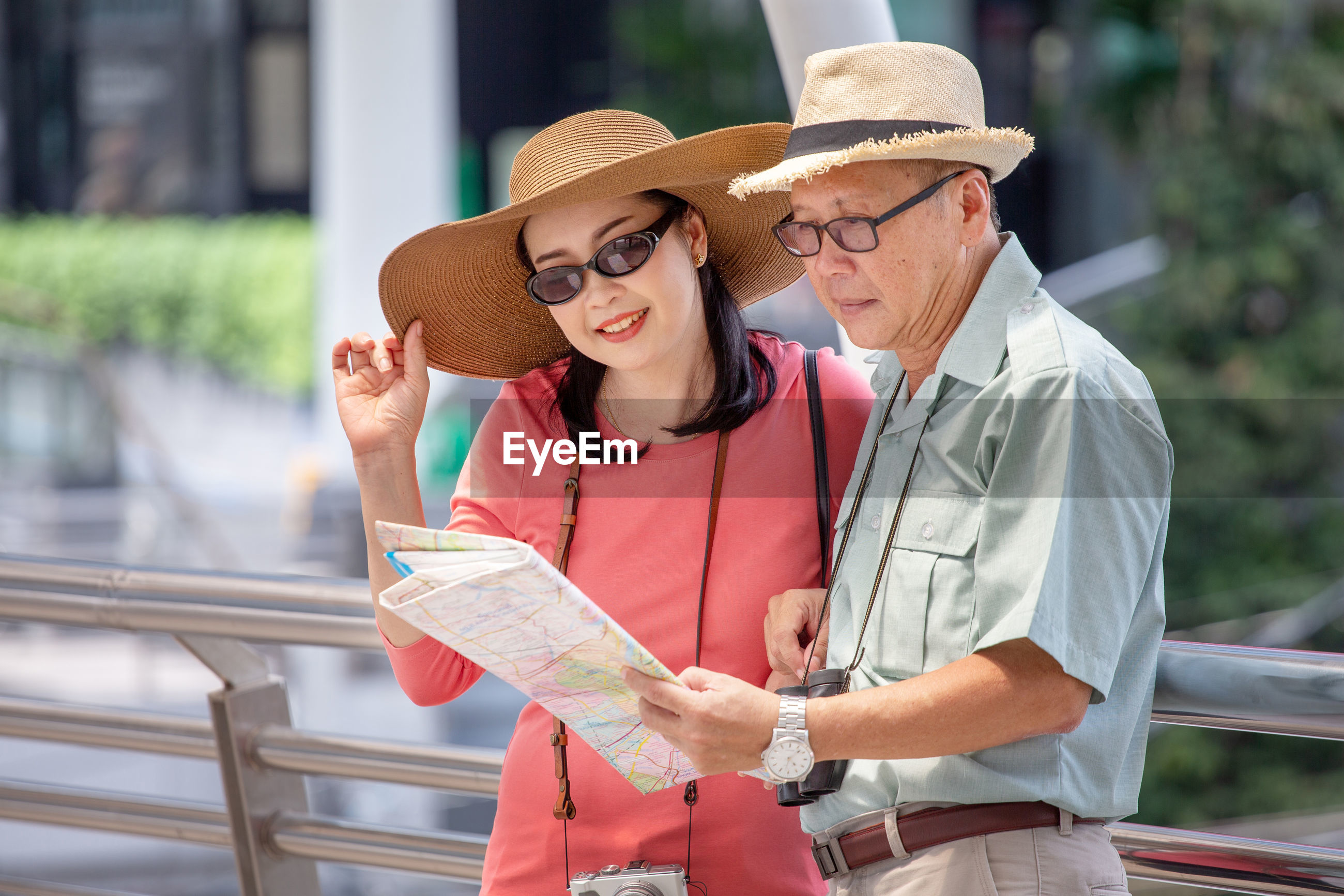 Couple reading map while standing in city