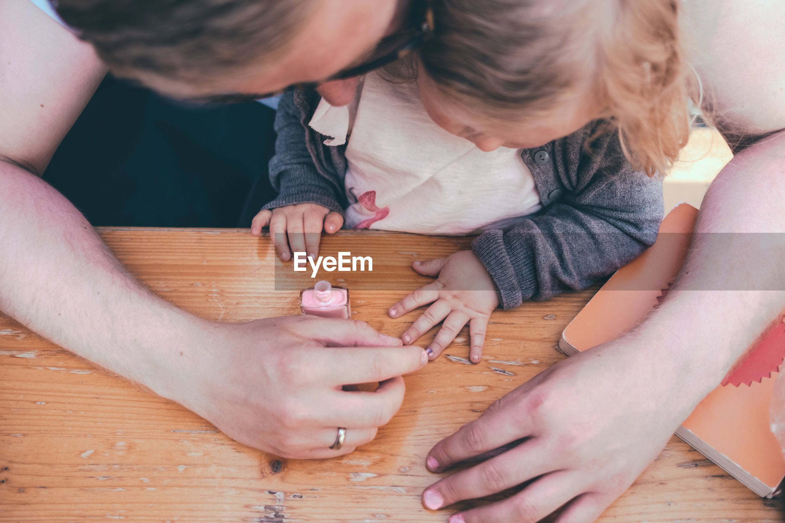 High angle view of father painting daughter fingernails on table outdoors