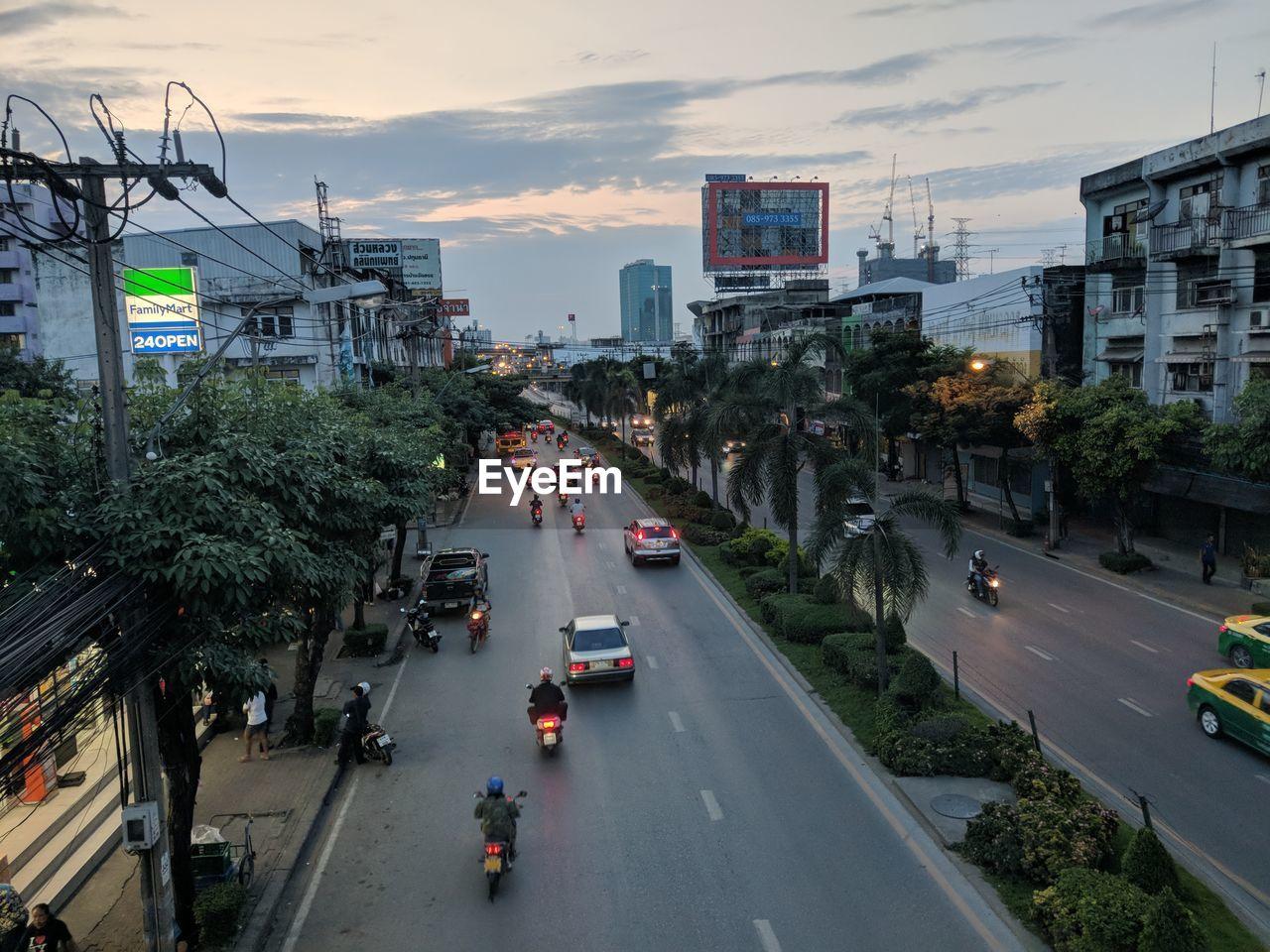city, transportation, road, car, street, mode of transportation, motor vehicle, land vehicle, architecture, building exterior, built structure, traffic, sky, city street, city life, cloud - sky, high angle view, sunset, nature, sign, outdoors, cityscape, skyscraper