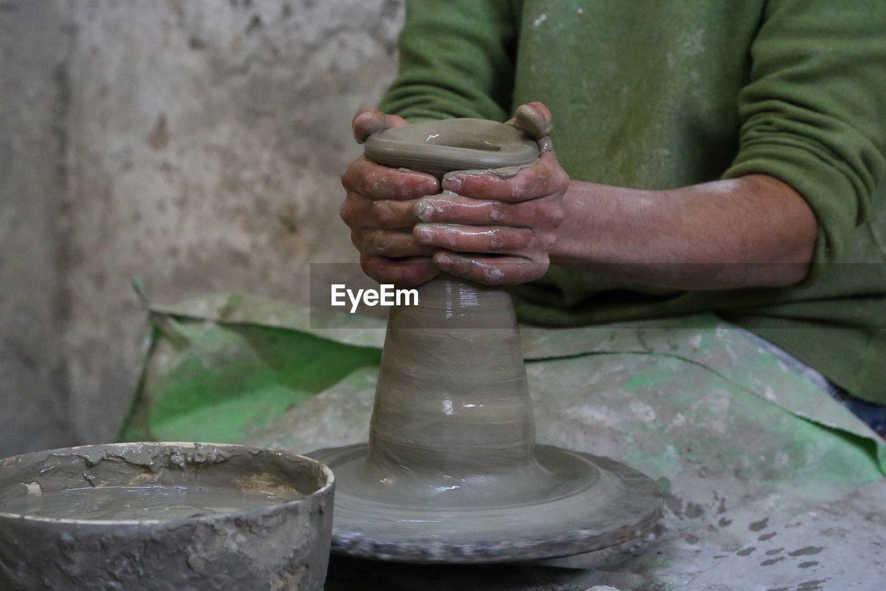 Midsection Of Male Potter Making Pot At Workshop