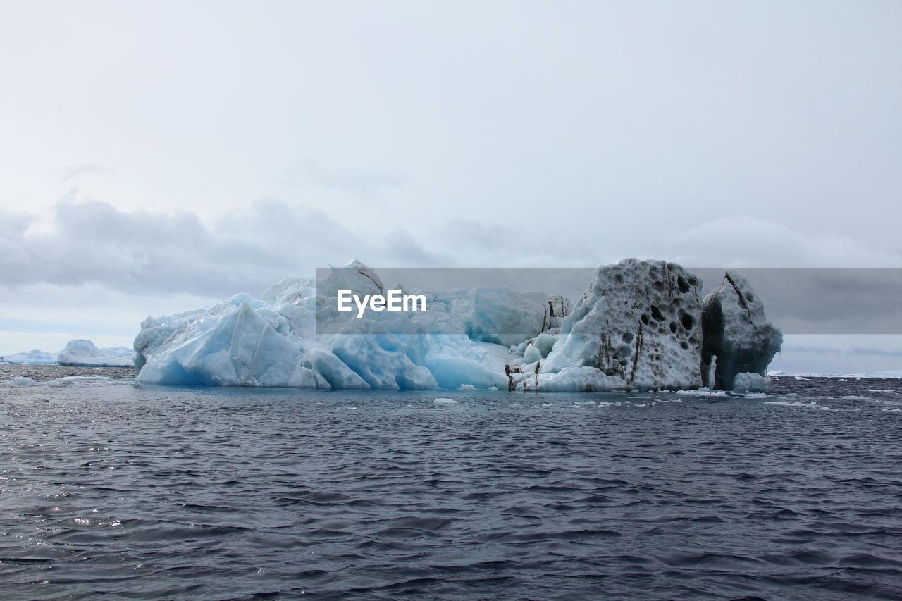 Iceberg In Sea Against Cloudy Sky