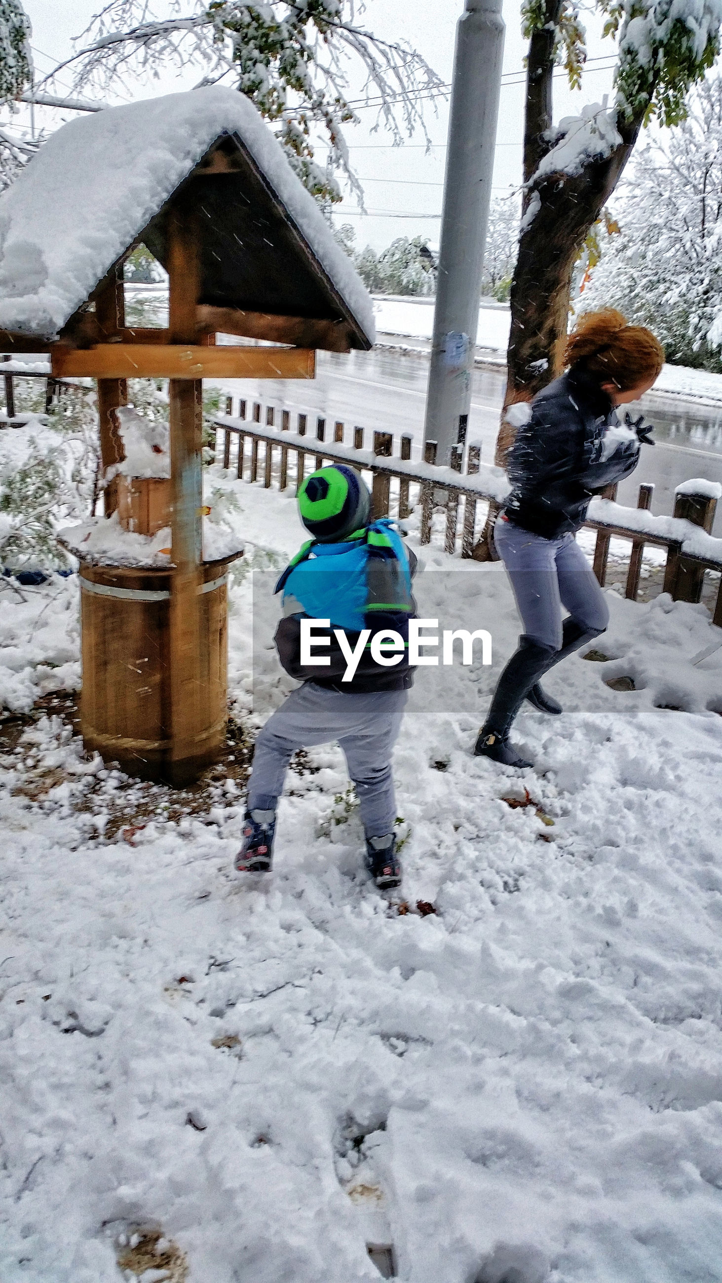 Mother and son playing in snow covered park