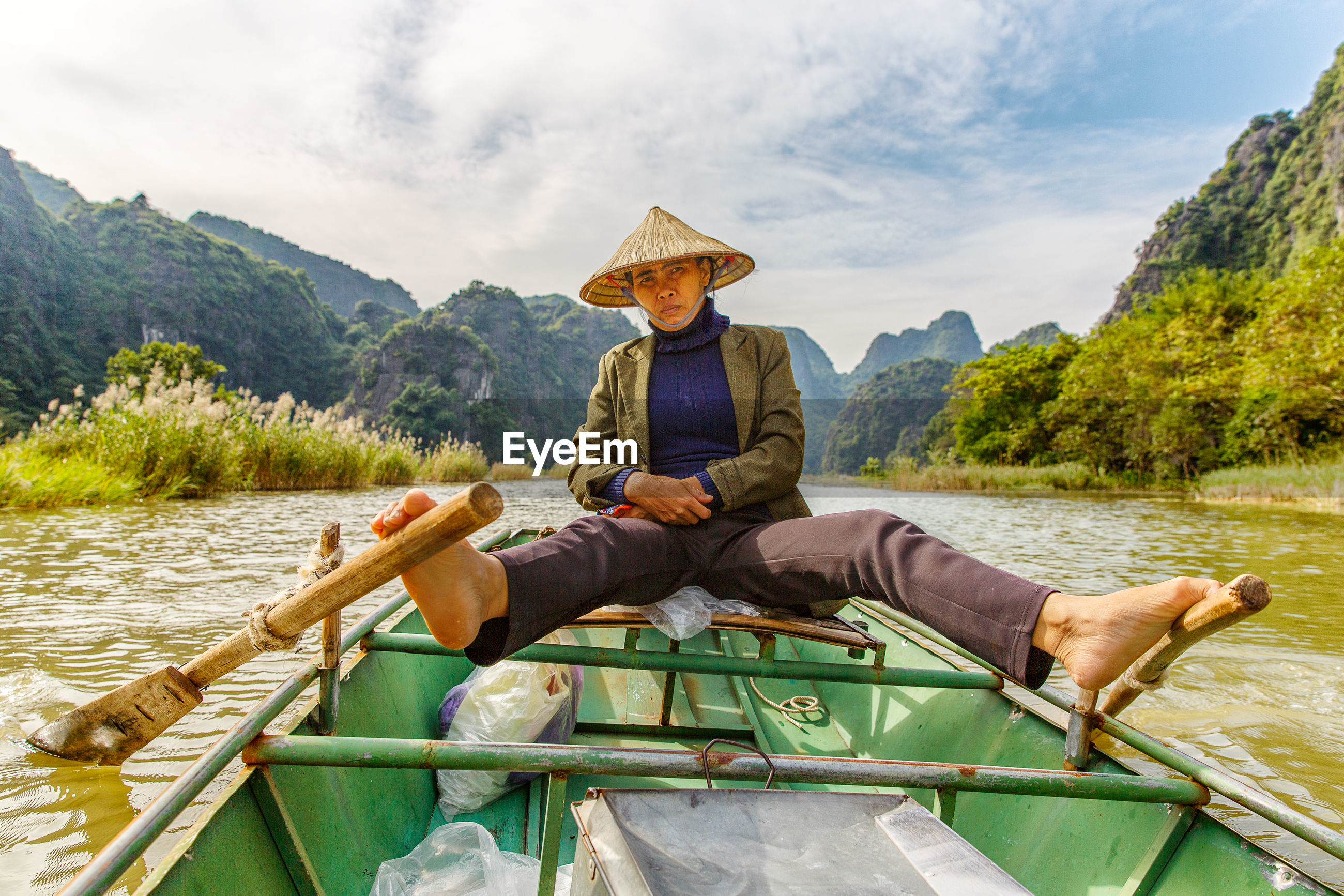 Portrait of female rower sailing on boat in river against sky
