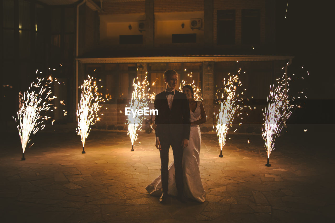 Full Length Of Bride And Bridegroom Standing By Firework Display At Night