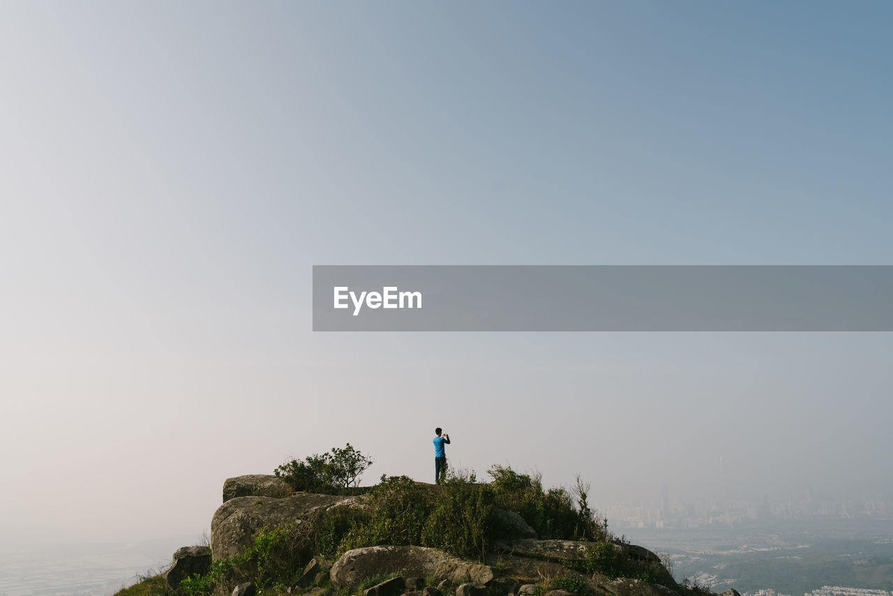 Man Standing On Mountain Peak Against Clear Sky