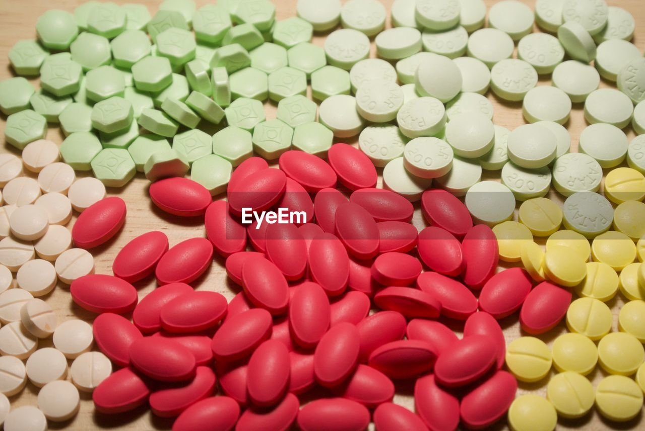 High angle view of colorful medicines on wooden table