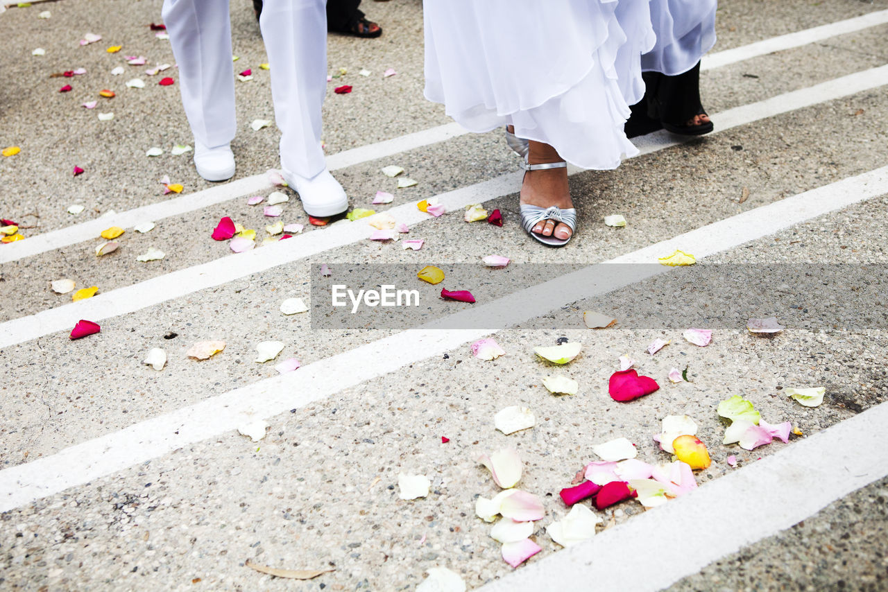 Low section of bride and groom walking on rose petals at street