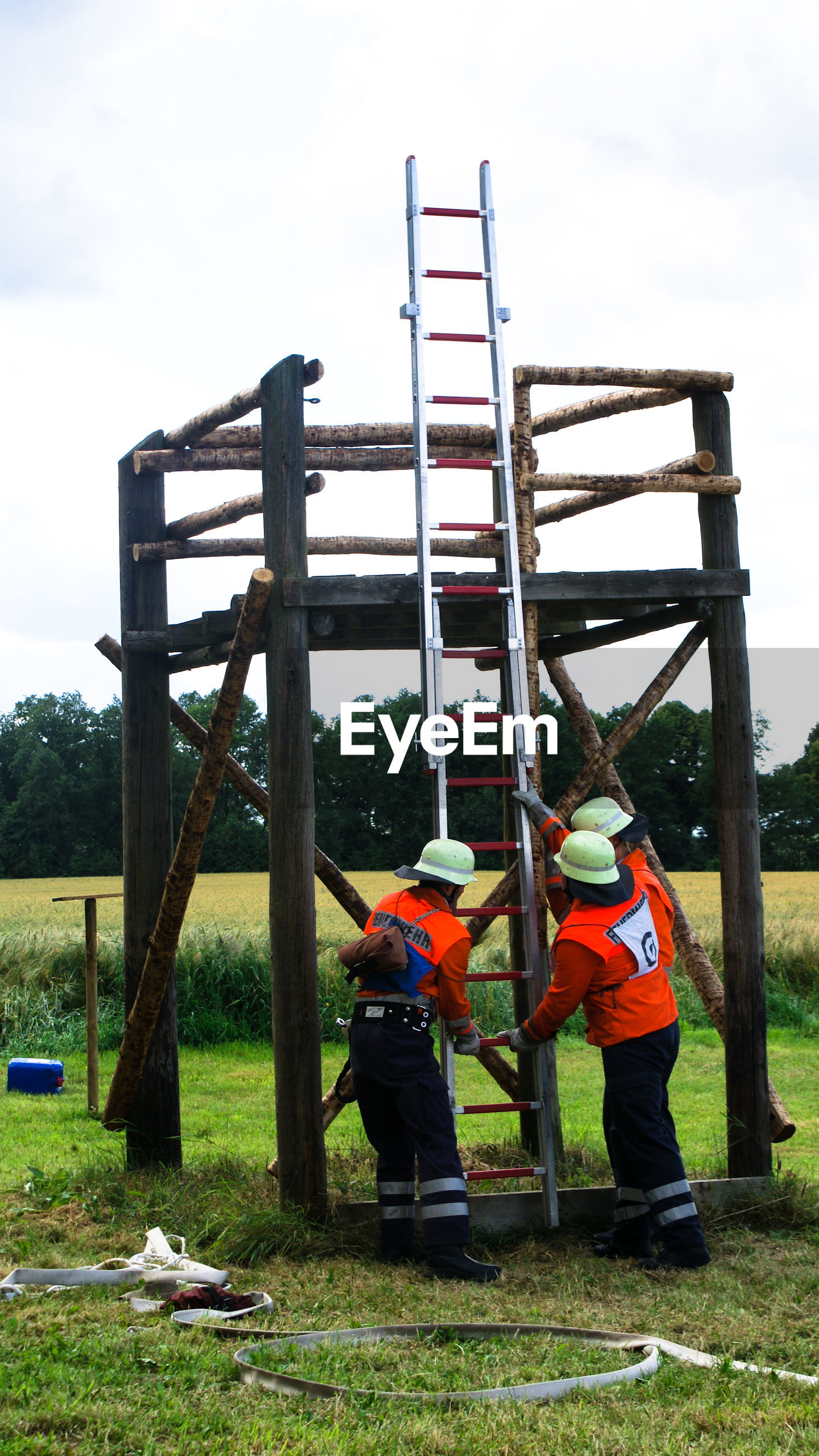 Firefighters holding ladder by built structure over grass field against sky