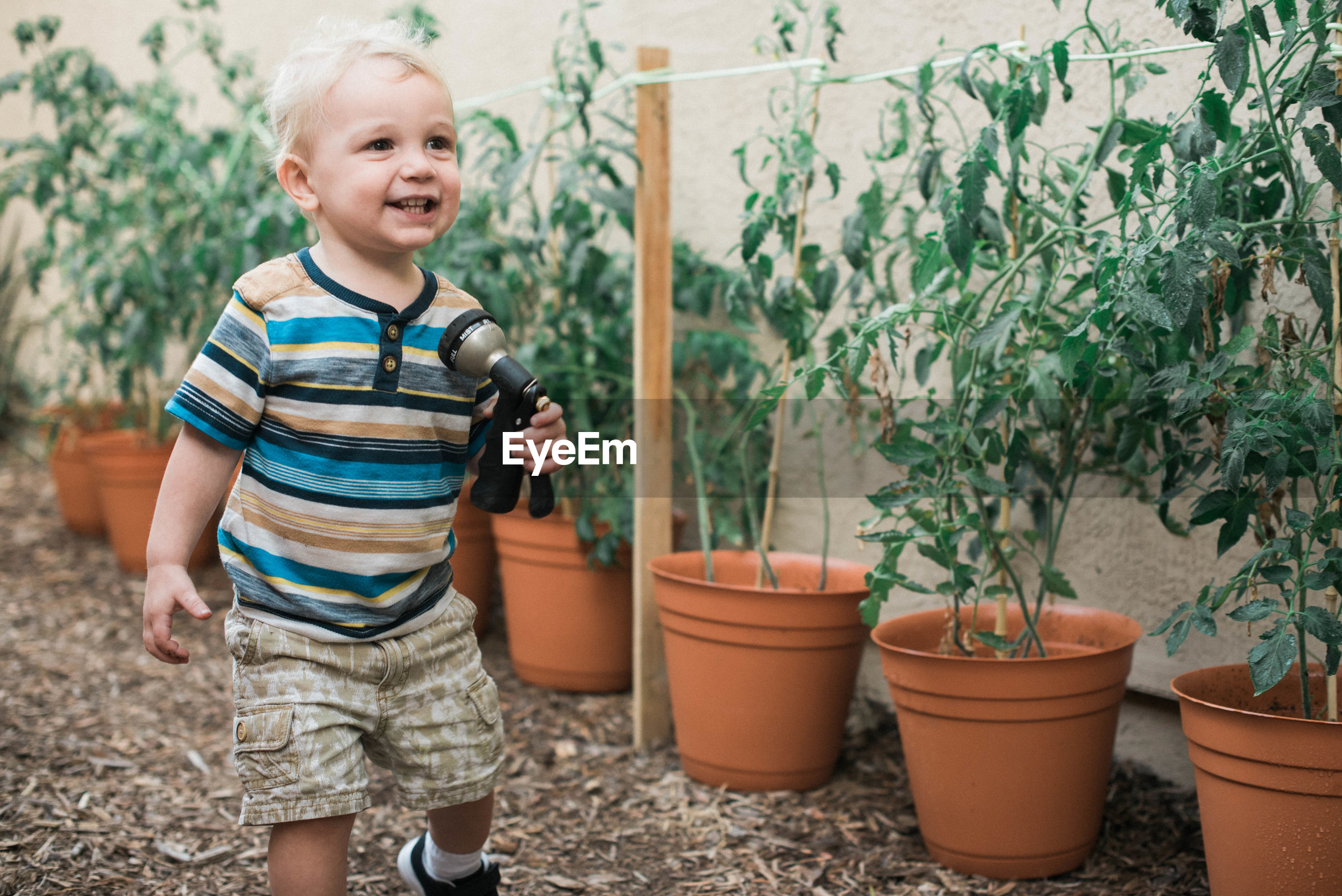 HAPPY BOY STANDING BY POTTED PLANT