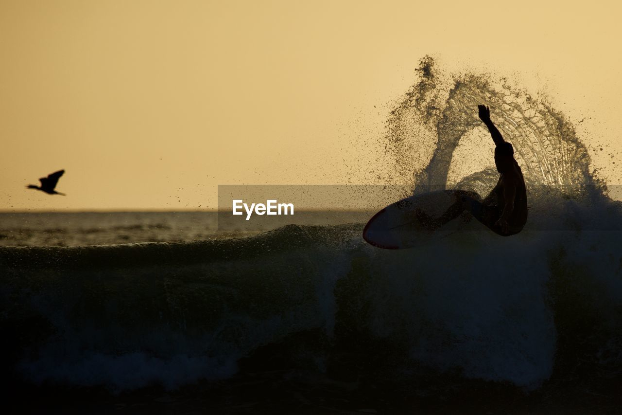 water, sunset, sea, sky, motion, nature, one person, silhouette, splashing, beauty in nature, leisure activity, real people, horizon over water, scenics - nature, land, horizon, men, outdoors, human arm, arms raised