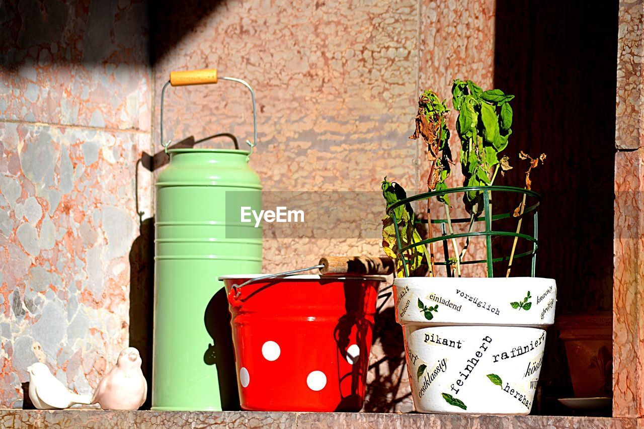 no people, container, potted plant, wall - building feature, day, built structure, nature, plant, still life, can, metal, garbage bin, architecture, outdoors, wall, red, green color, bucket, watering can, building exterior