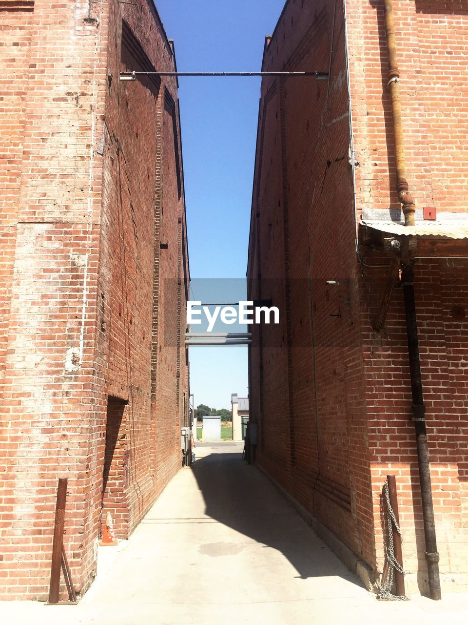 architecture, brick wall, built structure, building exterior, sunlight, day, shadow, outdoors, no people, the way forward, clear sky, sky, city
