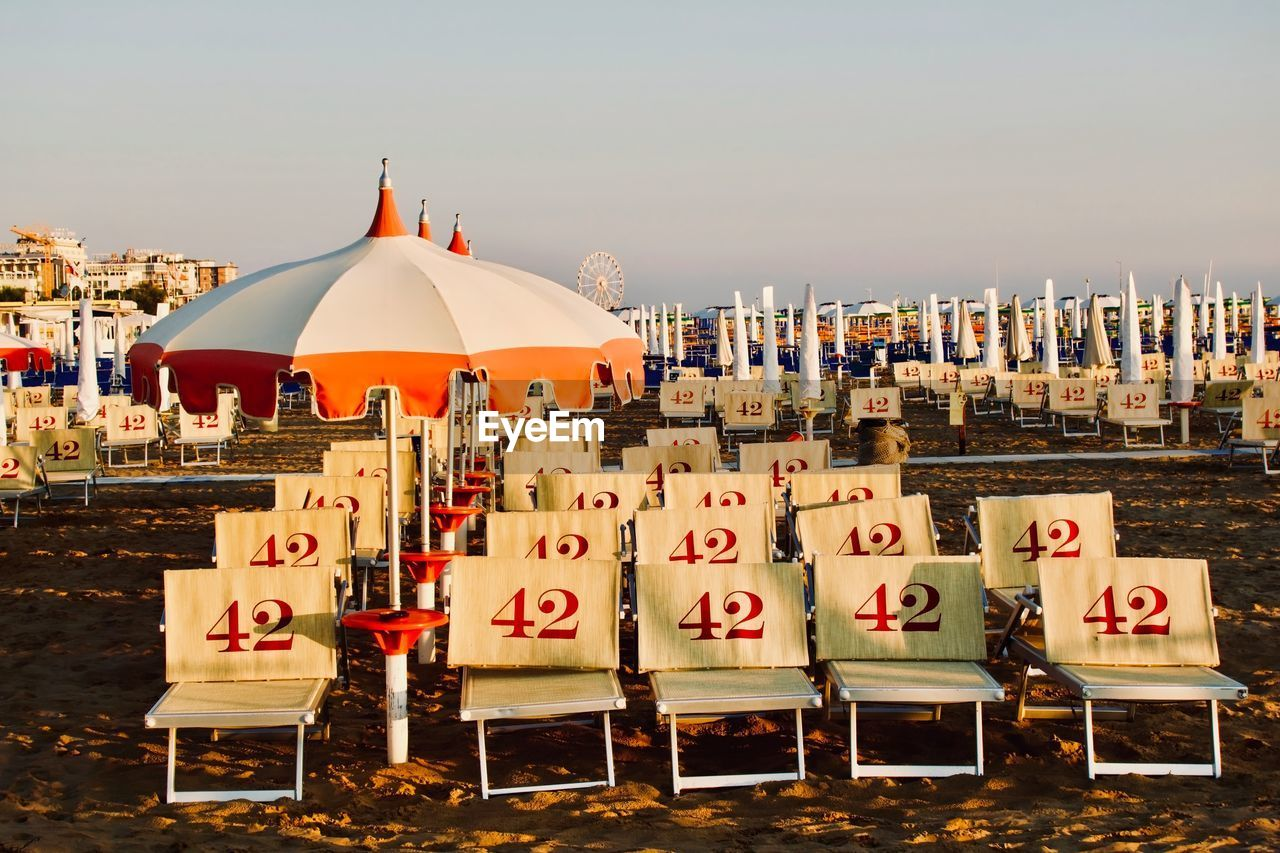 Beach umbrellas and numbered long chairs against sky during sunset