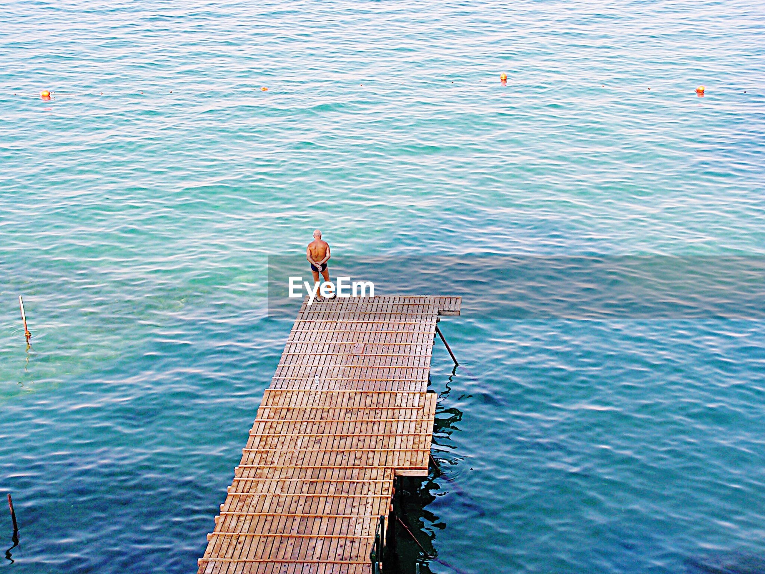 High angle view of shirtless senior man standing on jetty over sea