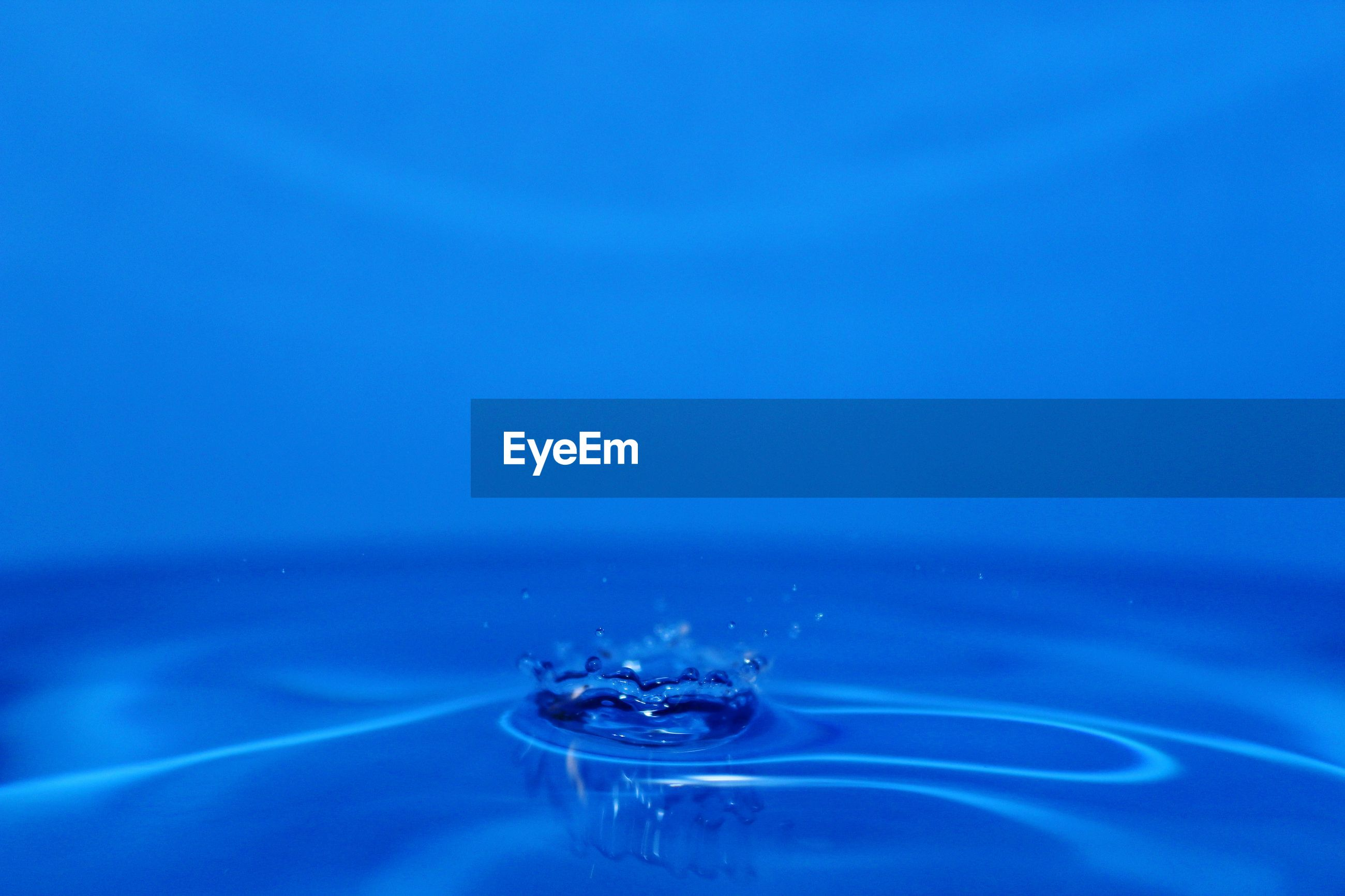 CLOSE-UP OF WATER SPLASHING ON BLUE SURFACE