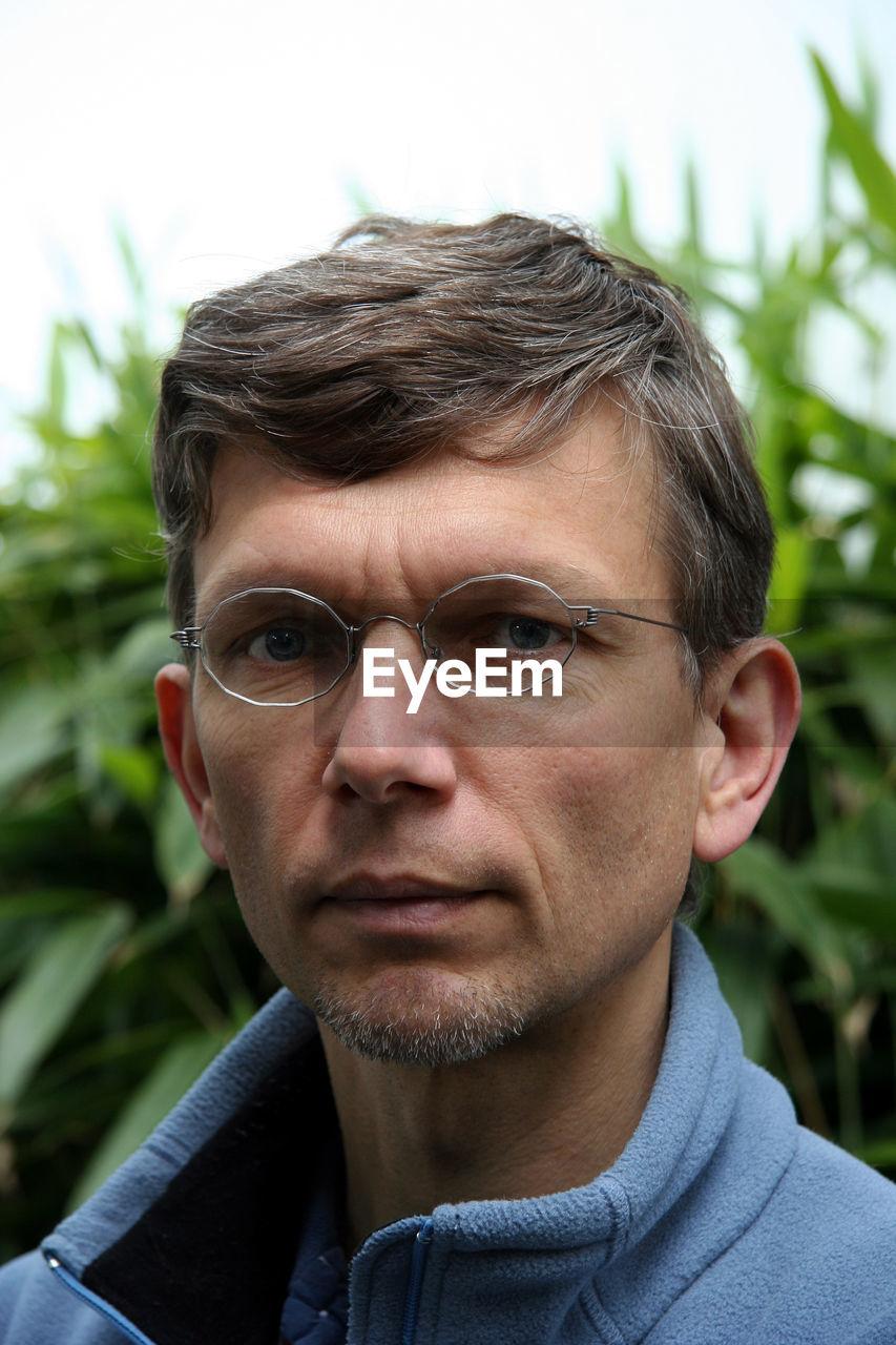 Portrait Of Mature Man Wearing Eyeglasses Against Plants