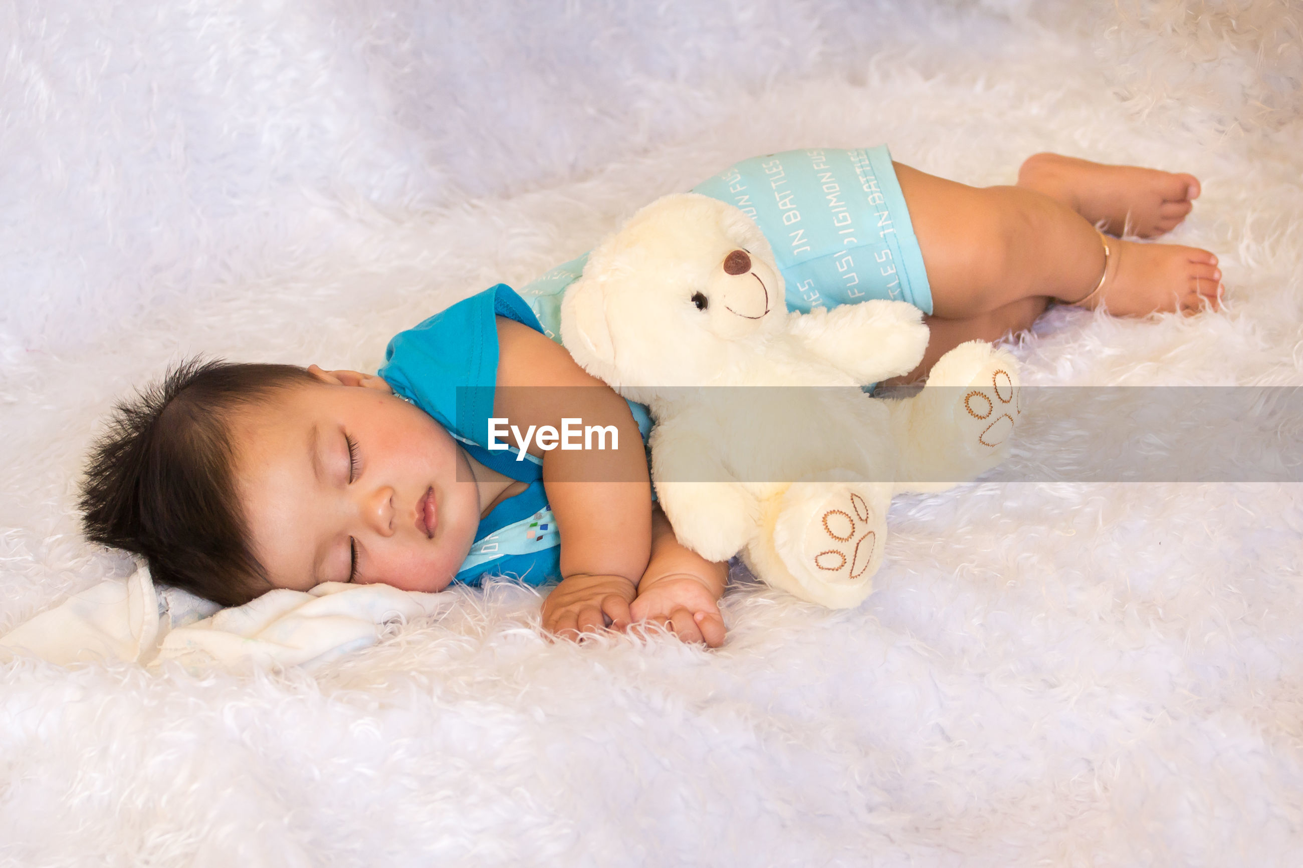 High angle view of cute baby boy sleeping on fur sheet at home