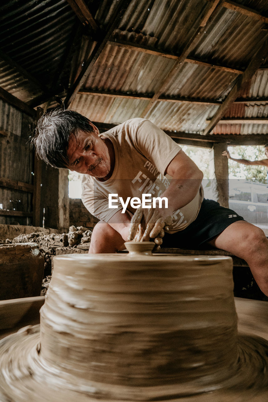 art and craft, one person, occupation, indoors, men, skill, real people, working, craft, workshop, creativity, pottery, craftsperson, making, expertise, adult, clay, motion, spinning, mature men