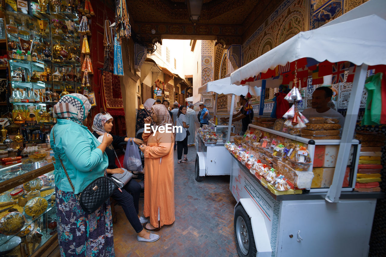 market, retail, group of people, real people, men, market stall, adult, women, food, food and drink, for sale, shopping, small business, business, architecture, people, store, built structure, lifestyles, selling, sale, vendor, buying, retail display, consumerism, street market