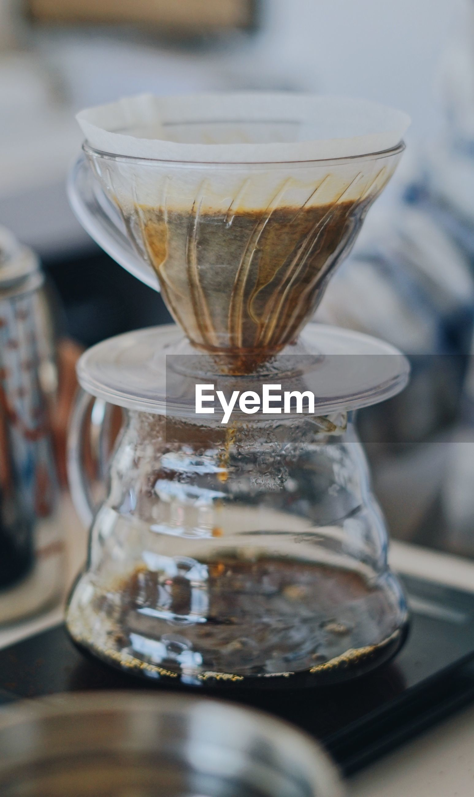 Close-up of black coffee in glass container on table during filtration